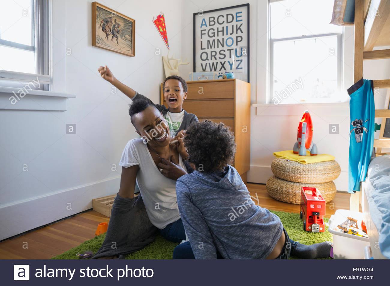 Madre jugando con sus hijos en el dormitorio Imagen De Stock