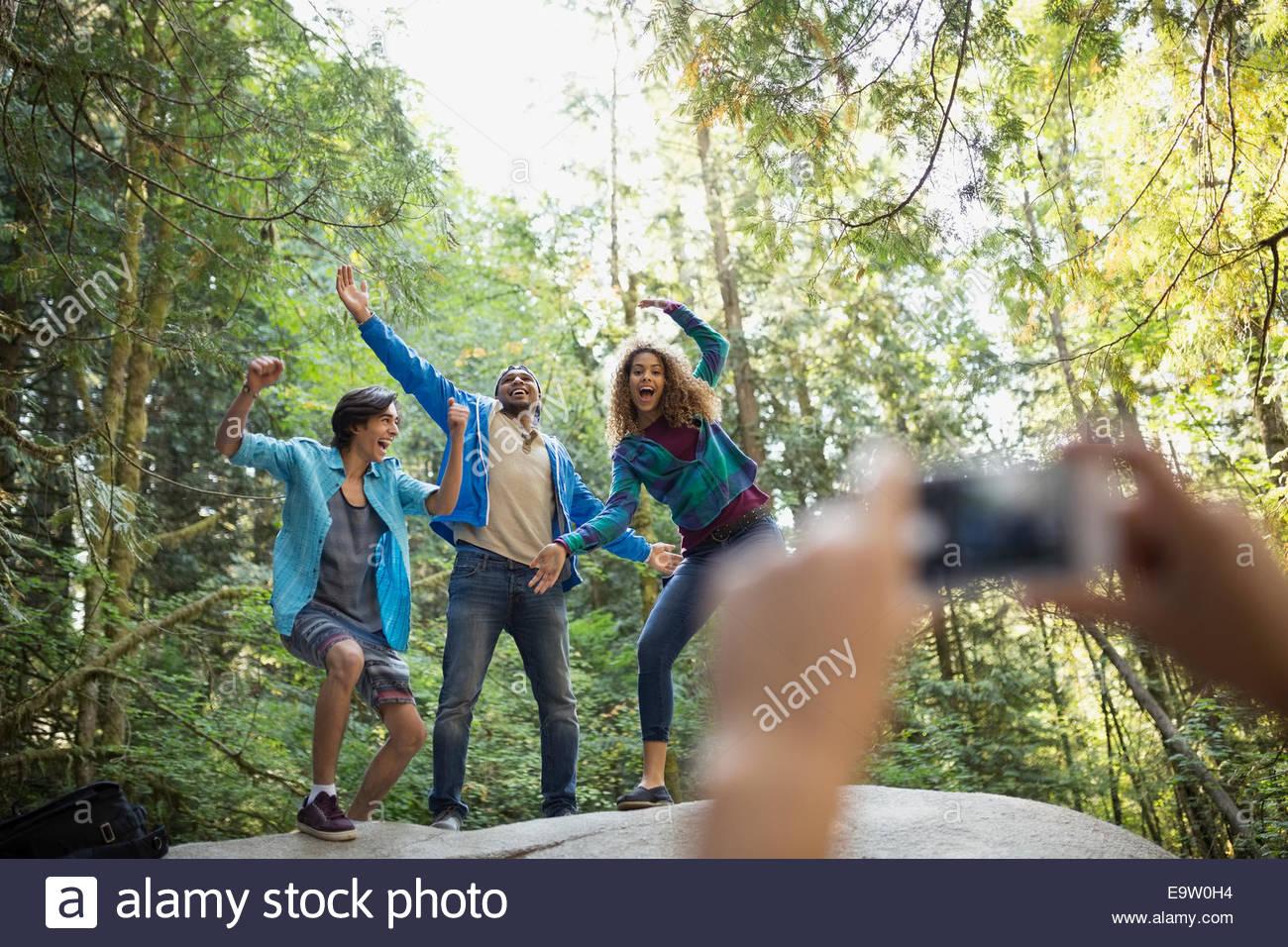 Amigos alegremente posando para fotografía en maderas Imagen De Stock