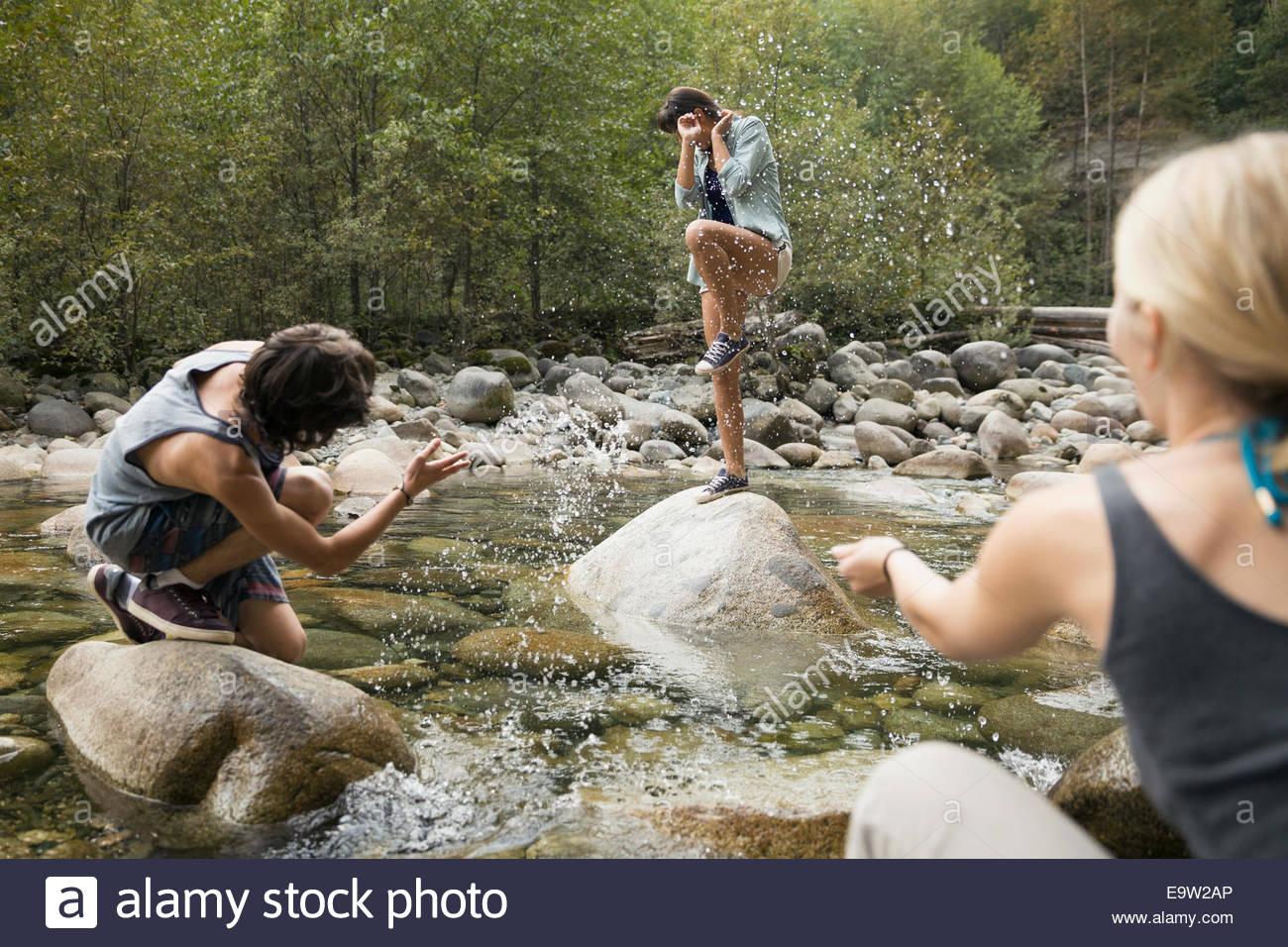Amigos salpicaduras de mujer en roca en creek Imagen De Stock
