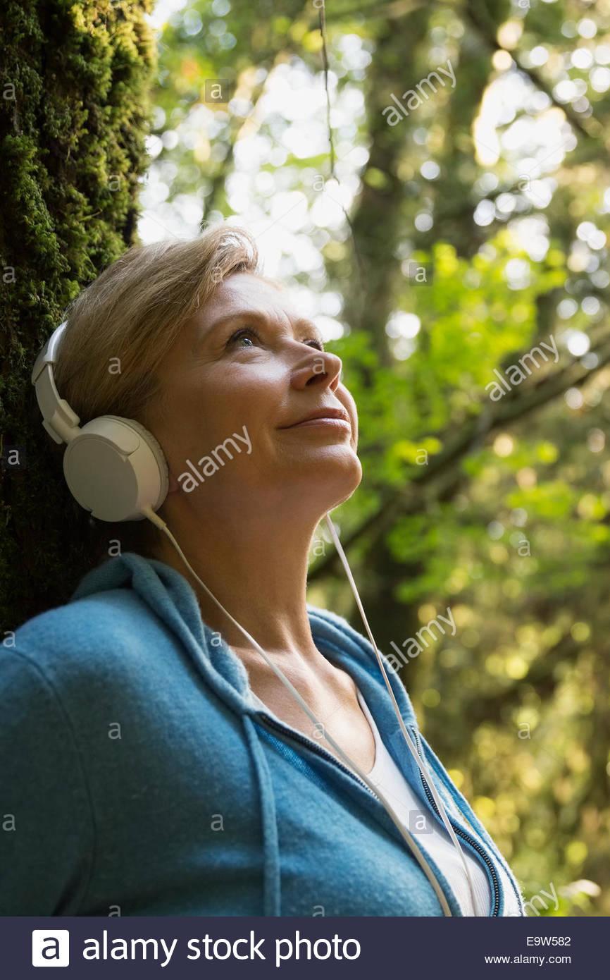 Mujer sonriente escuchando música en maderas Imagen De Stock