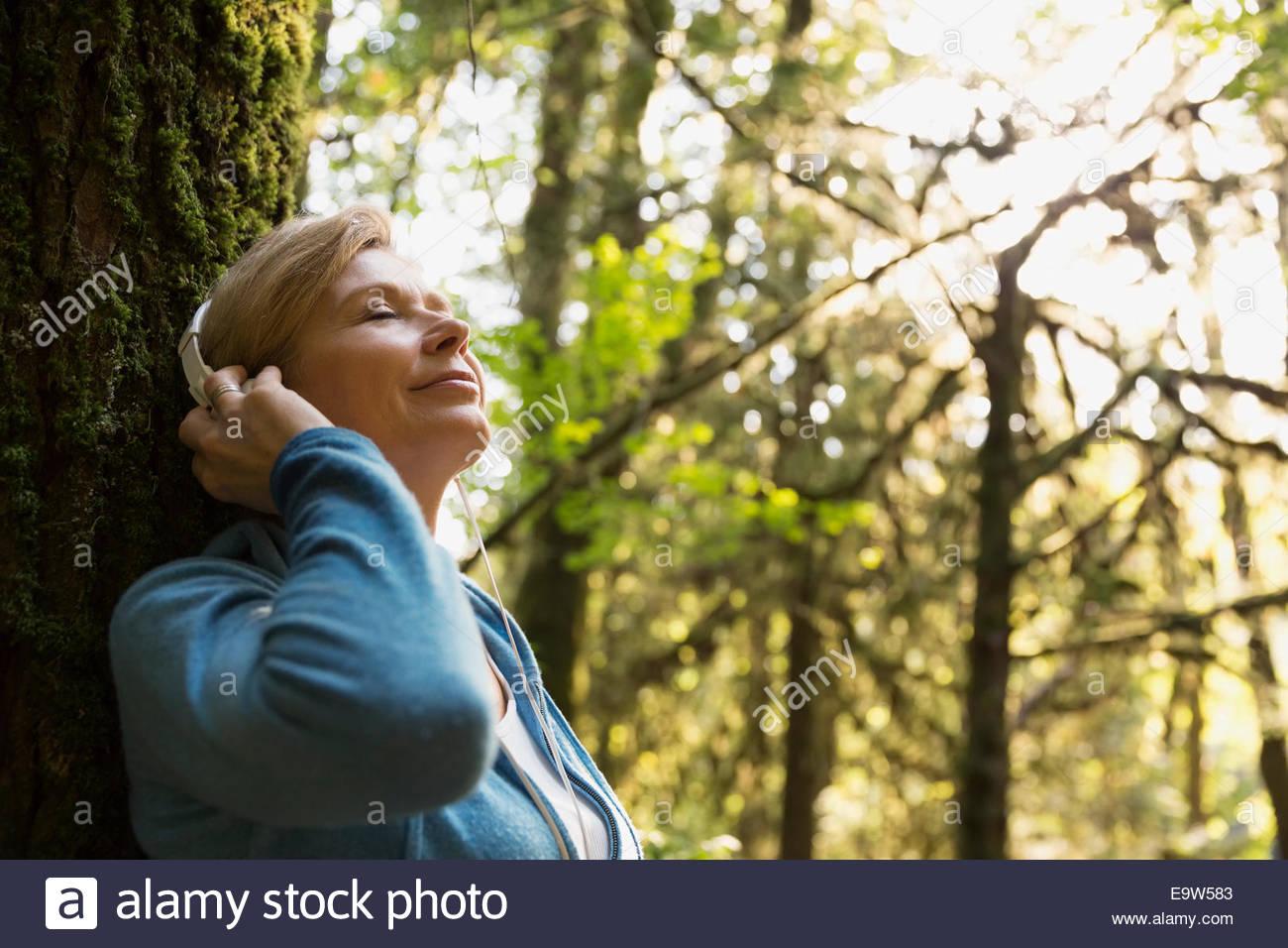 Serena mujer escuchando música en maderas Imagen De Stock