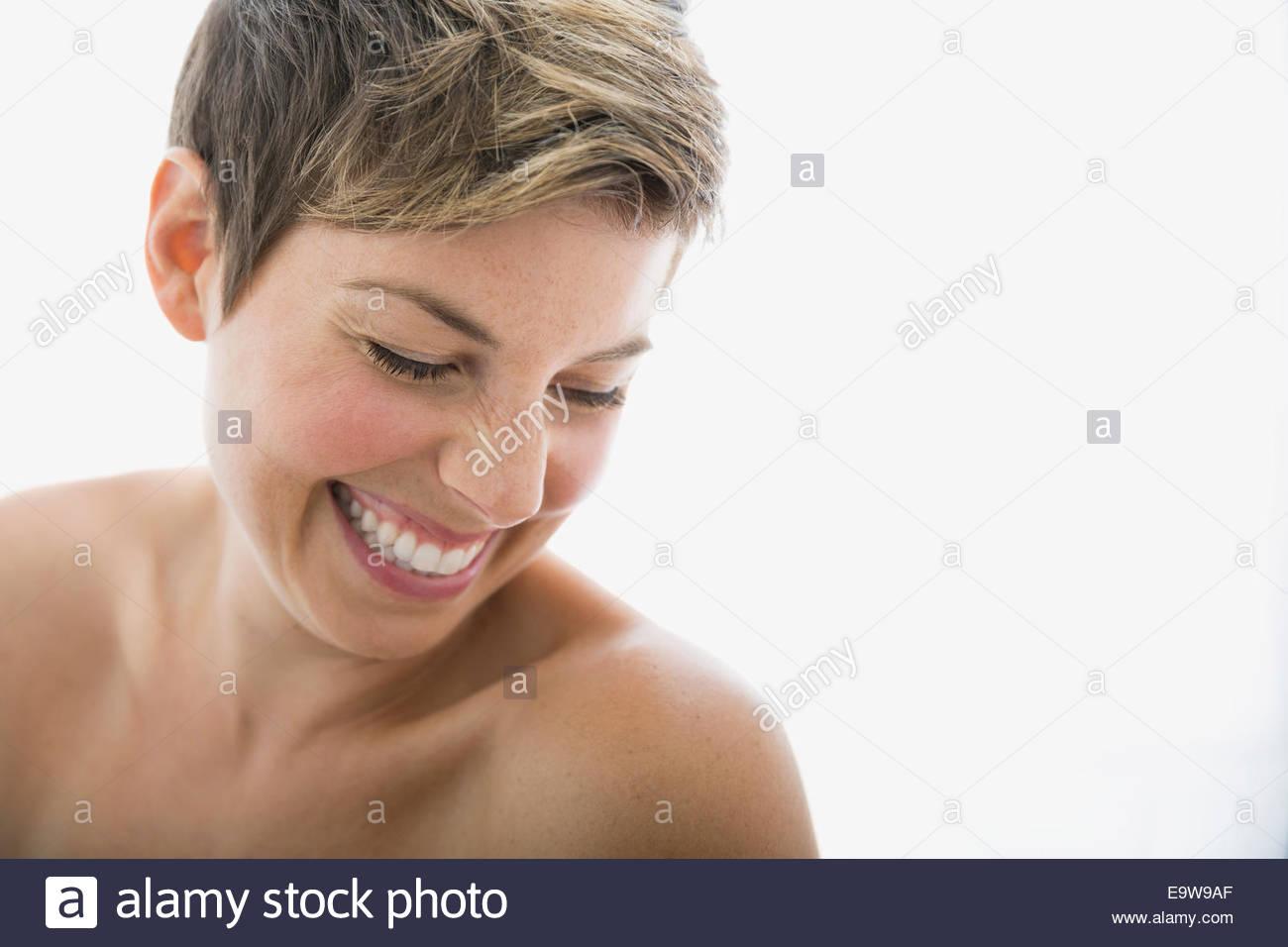 Laughing mujer con pecho desnudo mirando hacia abajo Imagen De Stock