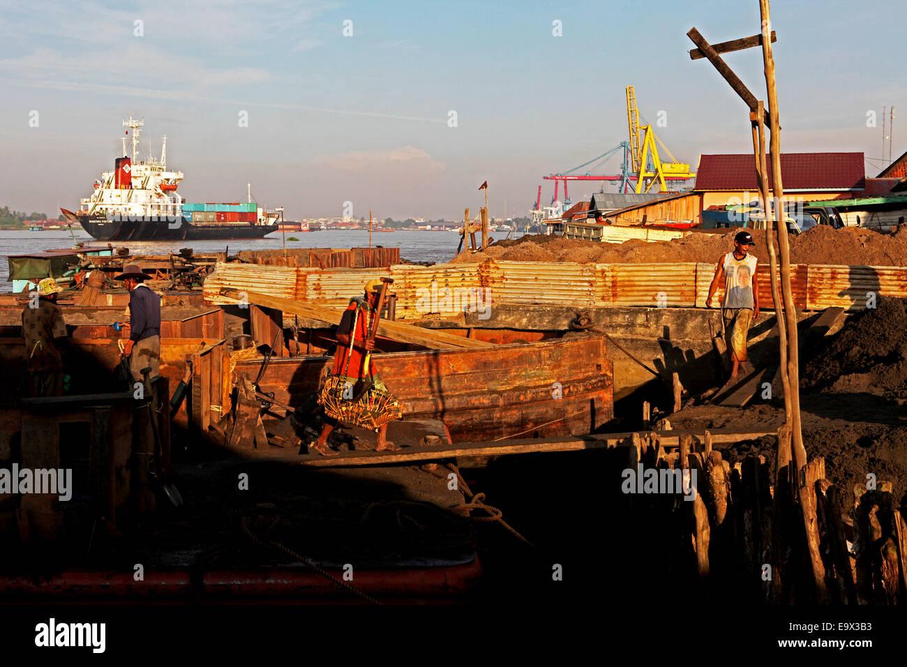 Los trabajadores cargando sands desde una barcaza mientras un buque de carga pasa a través del río Musi Imagen De Stock