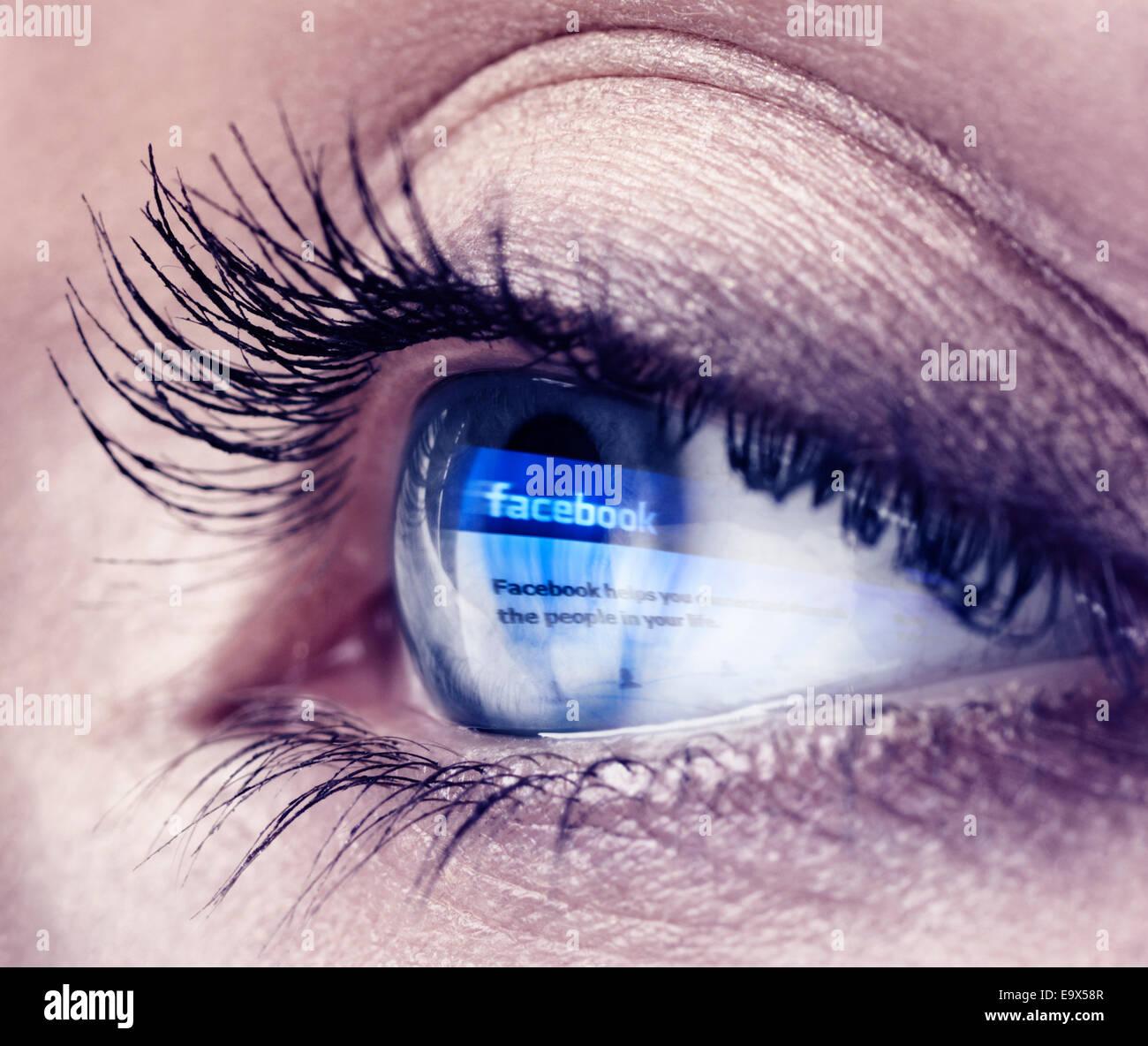 Primer plano de un joven del ojo azul con logotipo Facebook reflejando en ella Imagen De Stock