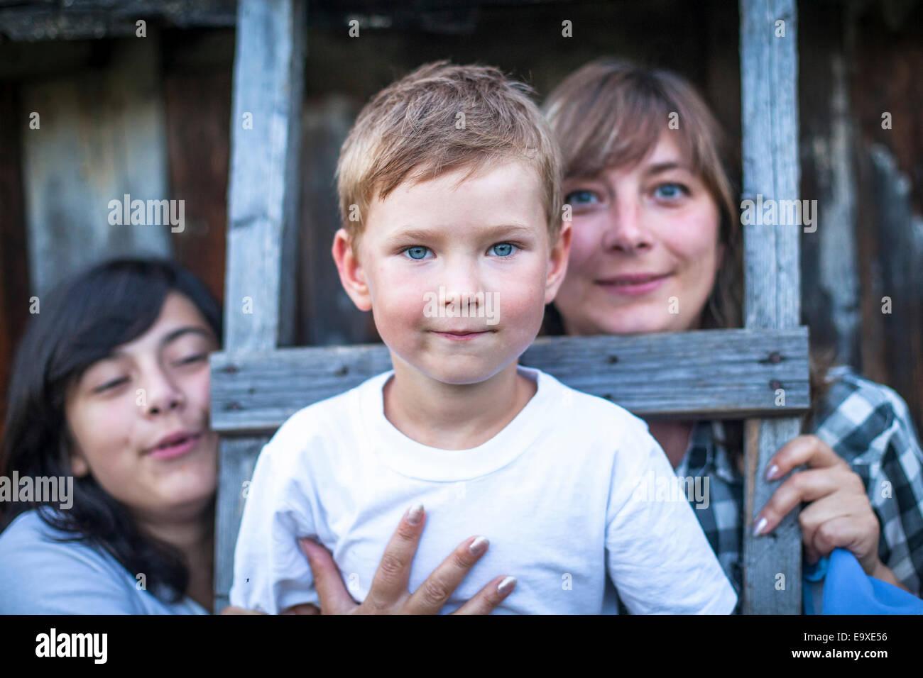 Retrato de un niño de cinco años, con su madre y su hermana mayor en el fondo. Imagen De Stock