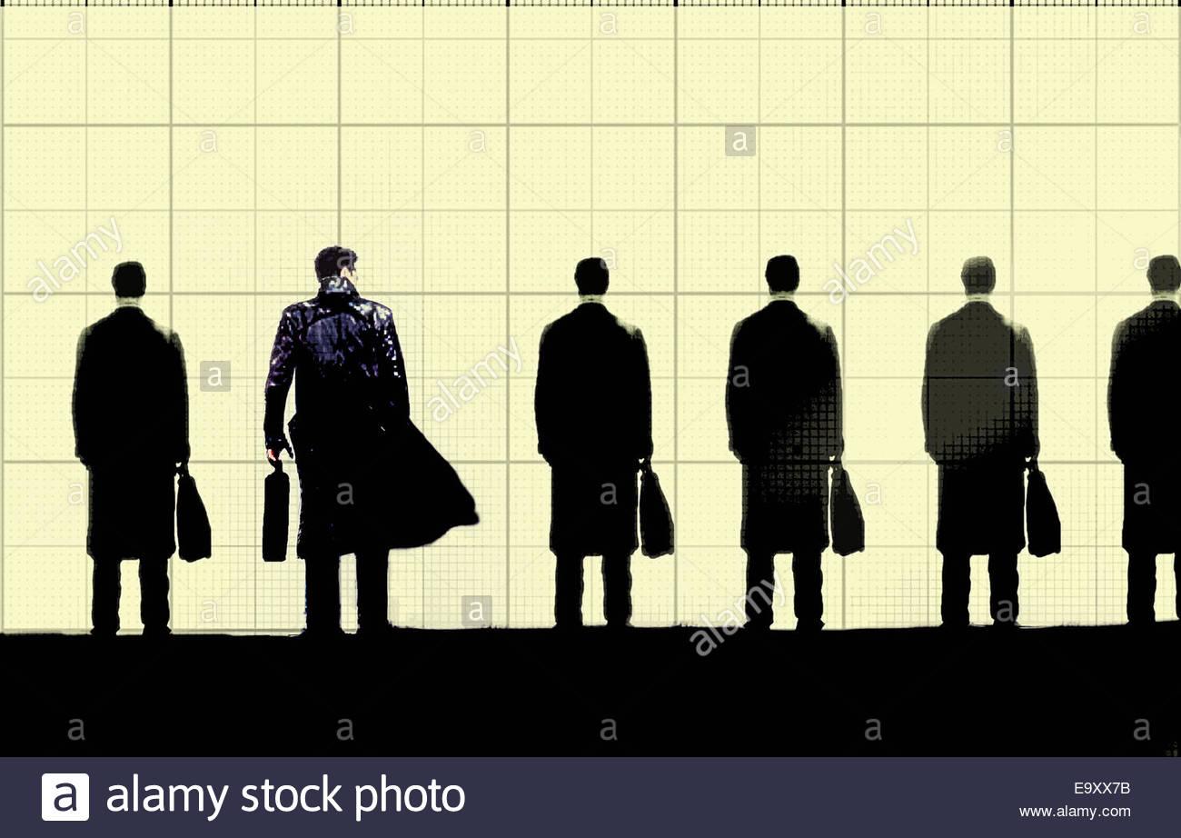 El empresario busca a empresarios similares de pie en una fila sosteniendo maletines Imagen De Stock
