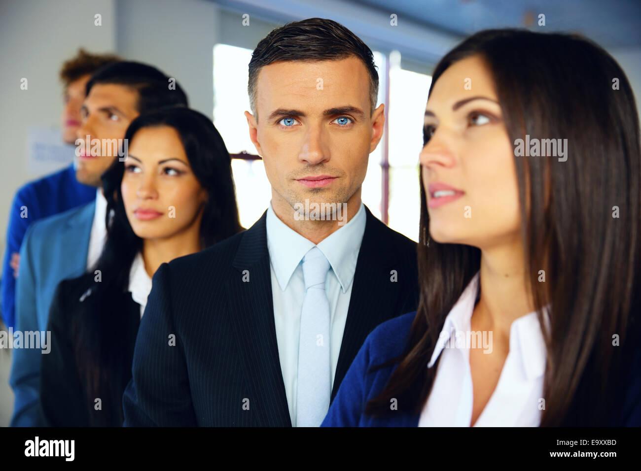 Un grupo de jóvenes empresarios graves de pie en la fila en la oficina Imagen De Stock