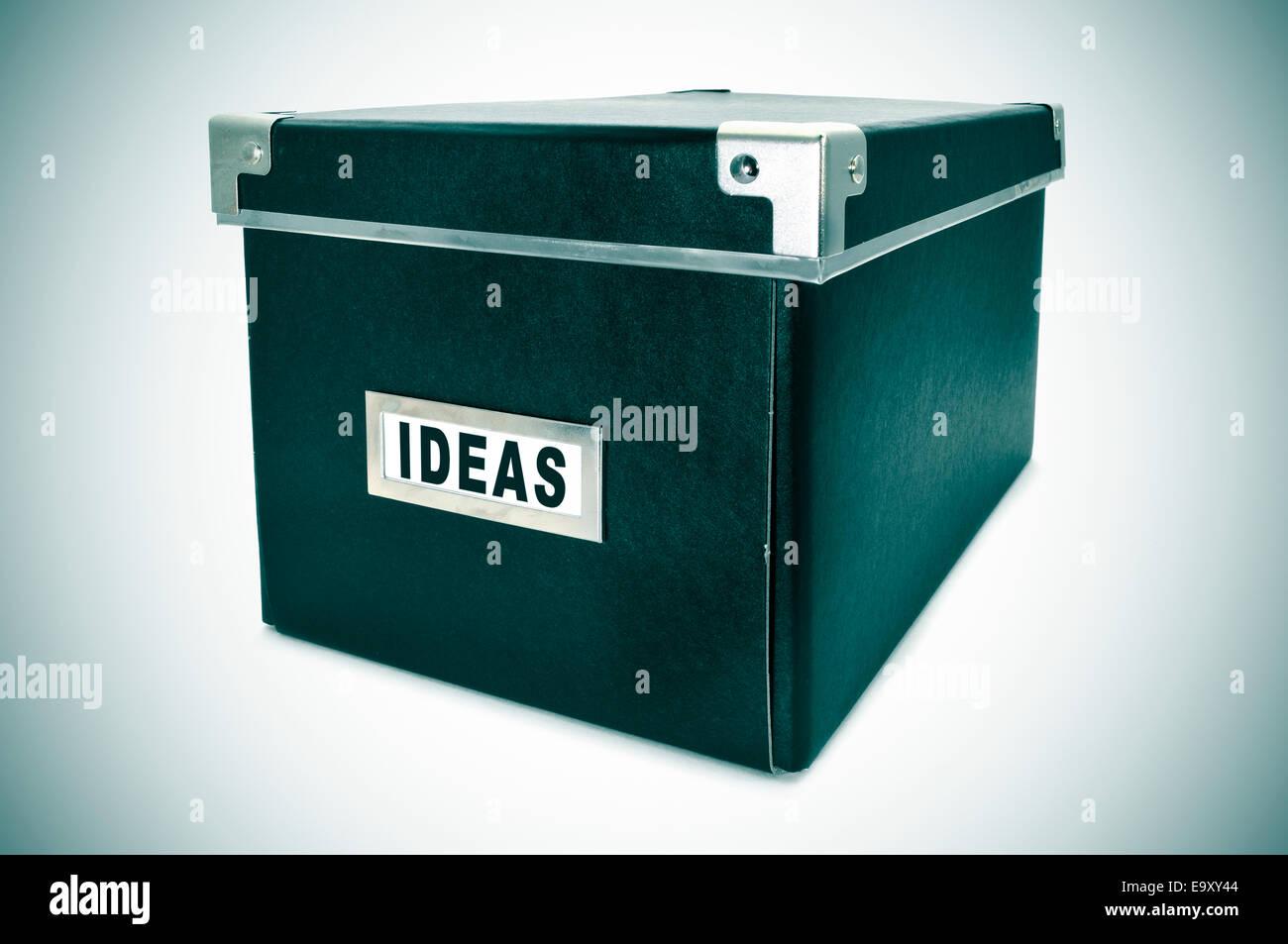 Una caja de almacenamiento de cartón negro con la palabra ideas por escrito en la tarjeta de índice Imagen De Stock