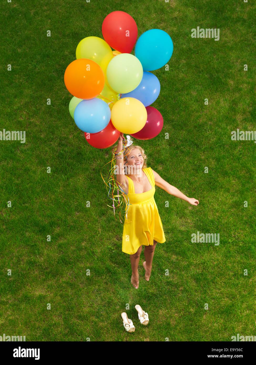 Joven Mujer feliz volando desde el suelo en coloridos globos de aire Imagen De Stock