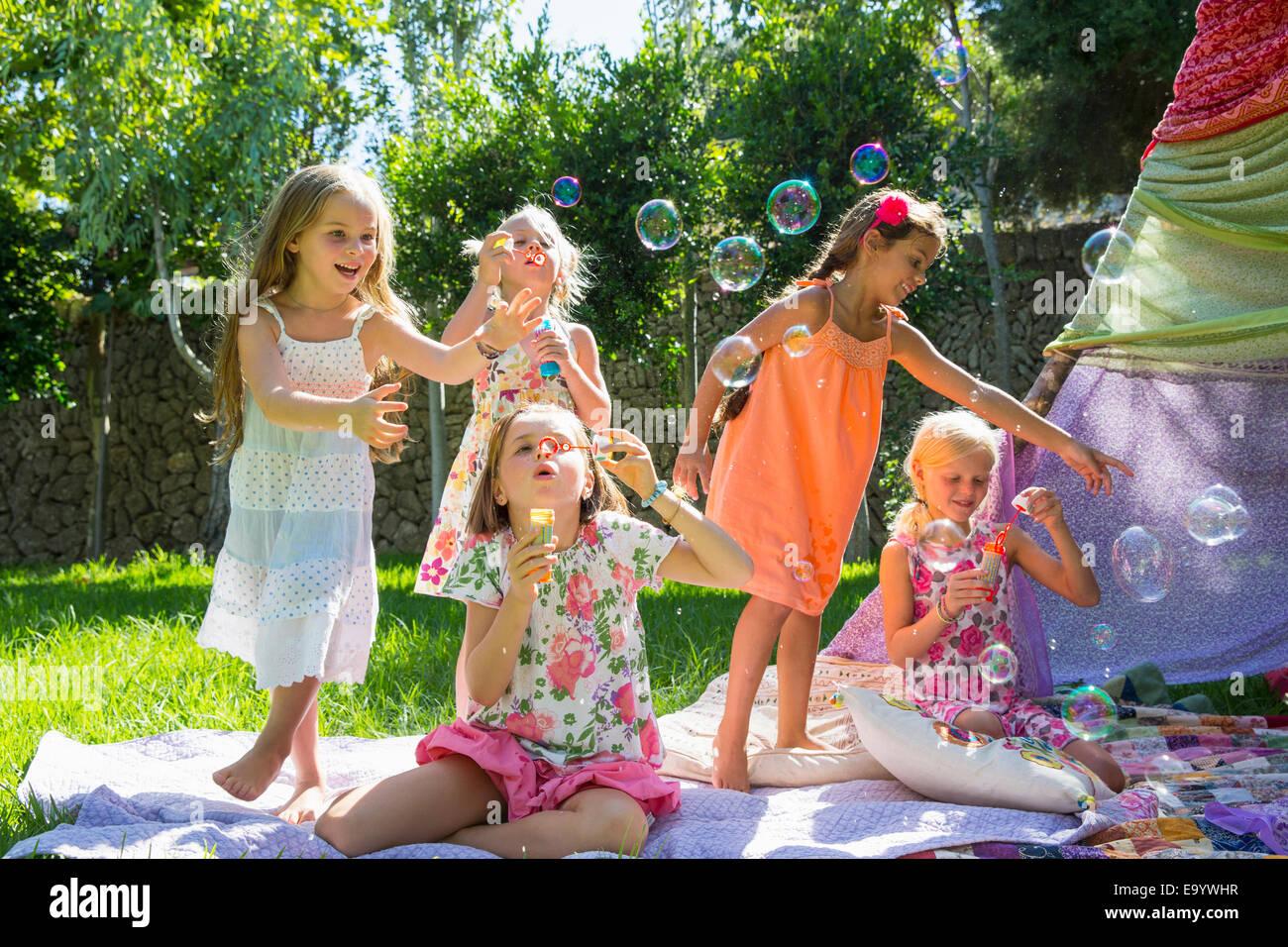 Las niñas soplando burbujas en verano garden party Imagen De Stock