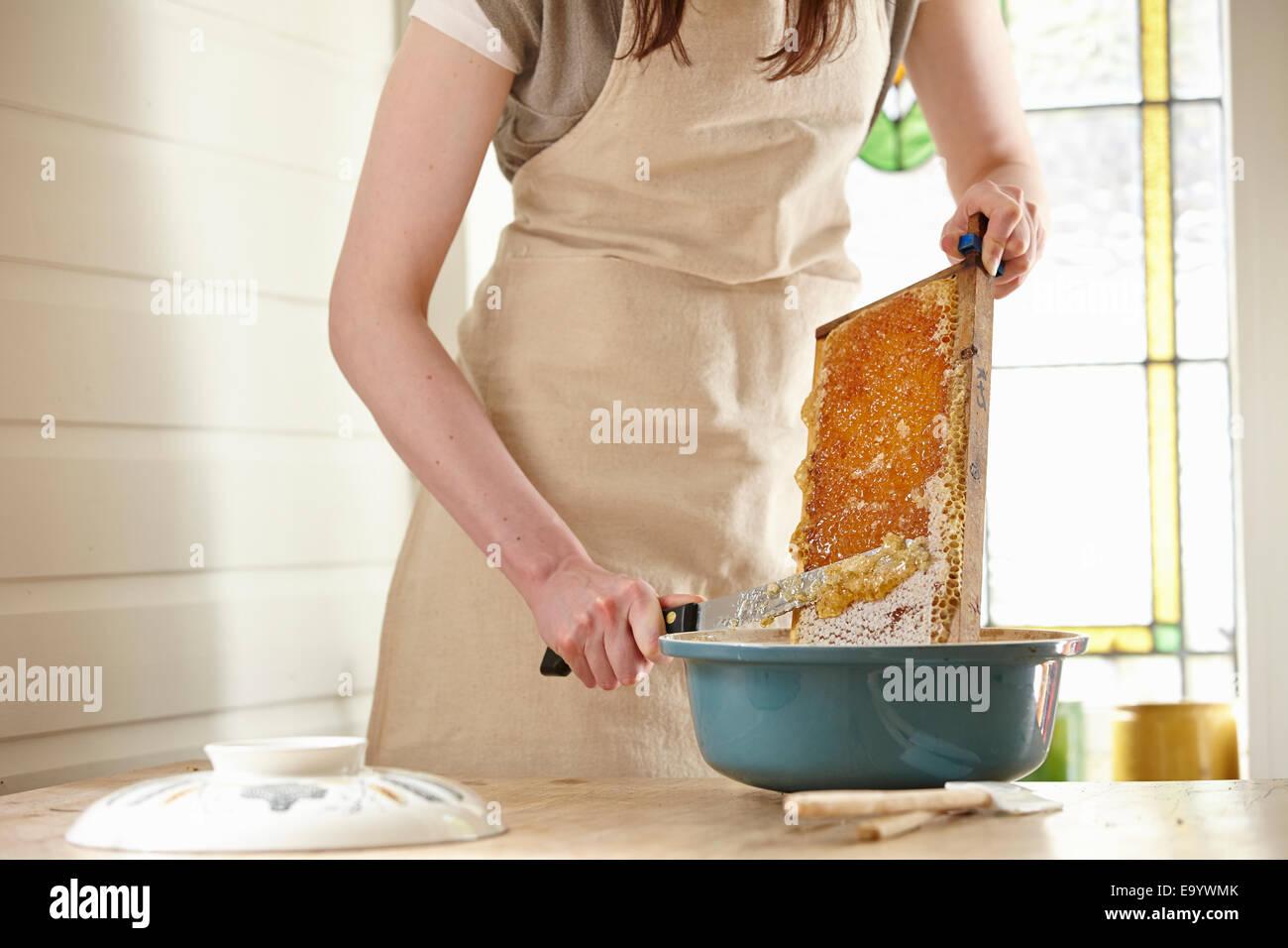 Apicultor femenino en cocina raspado 'super' (honeycomb bastidor) Imagen De Stock