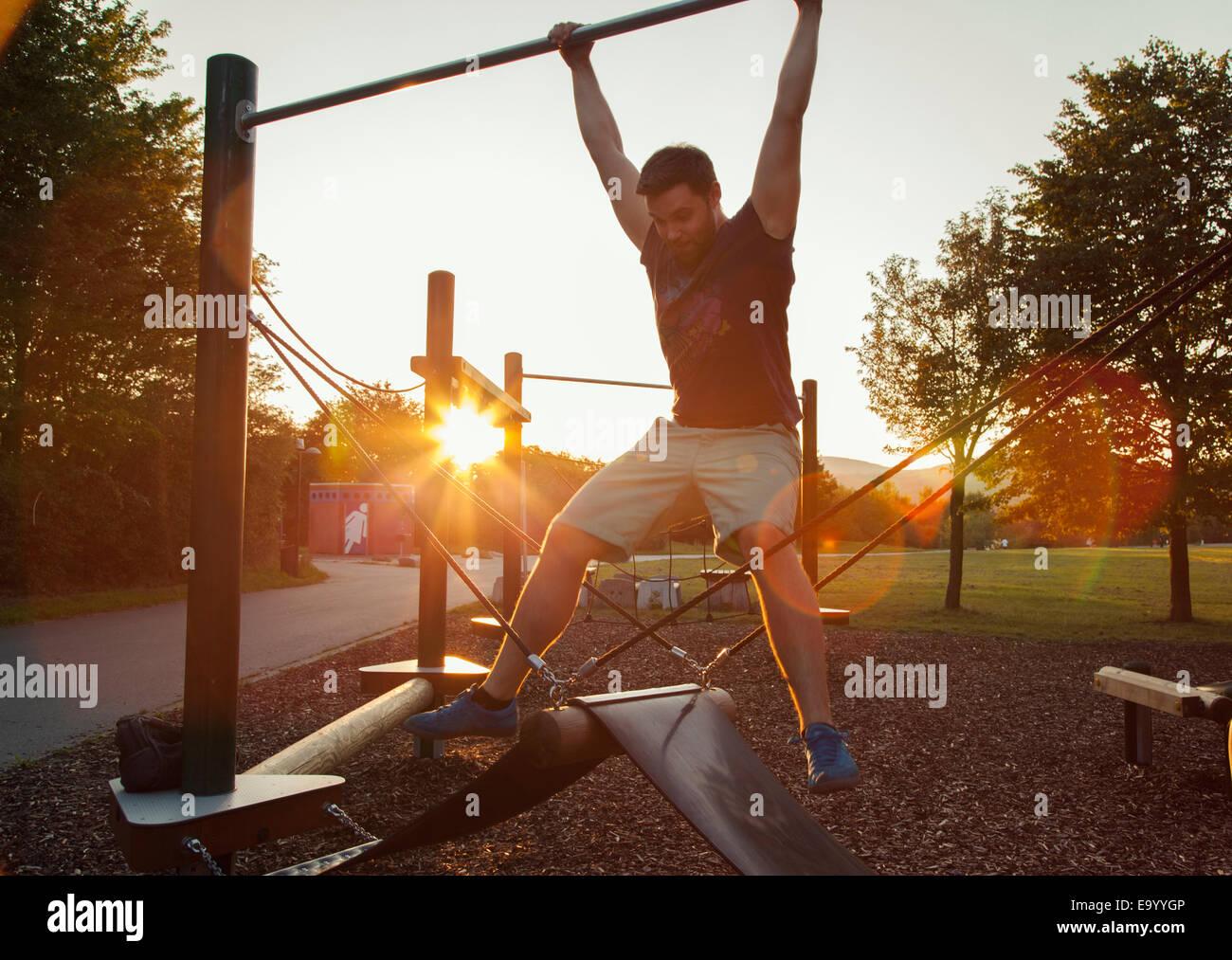 Siluetas de joven se balanceen en playground columpios al atardecer Imagen De Stock