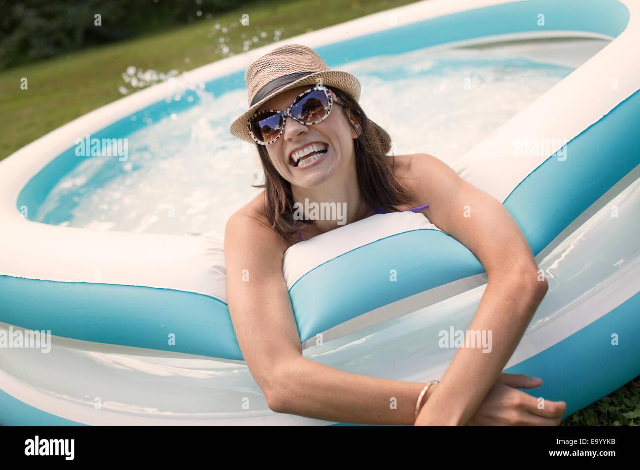 Mujer madura en piscina de chapoteo, las salpicaduras de agua. Imagen De Stock