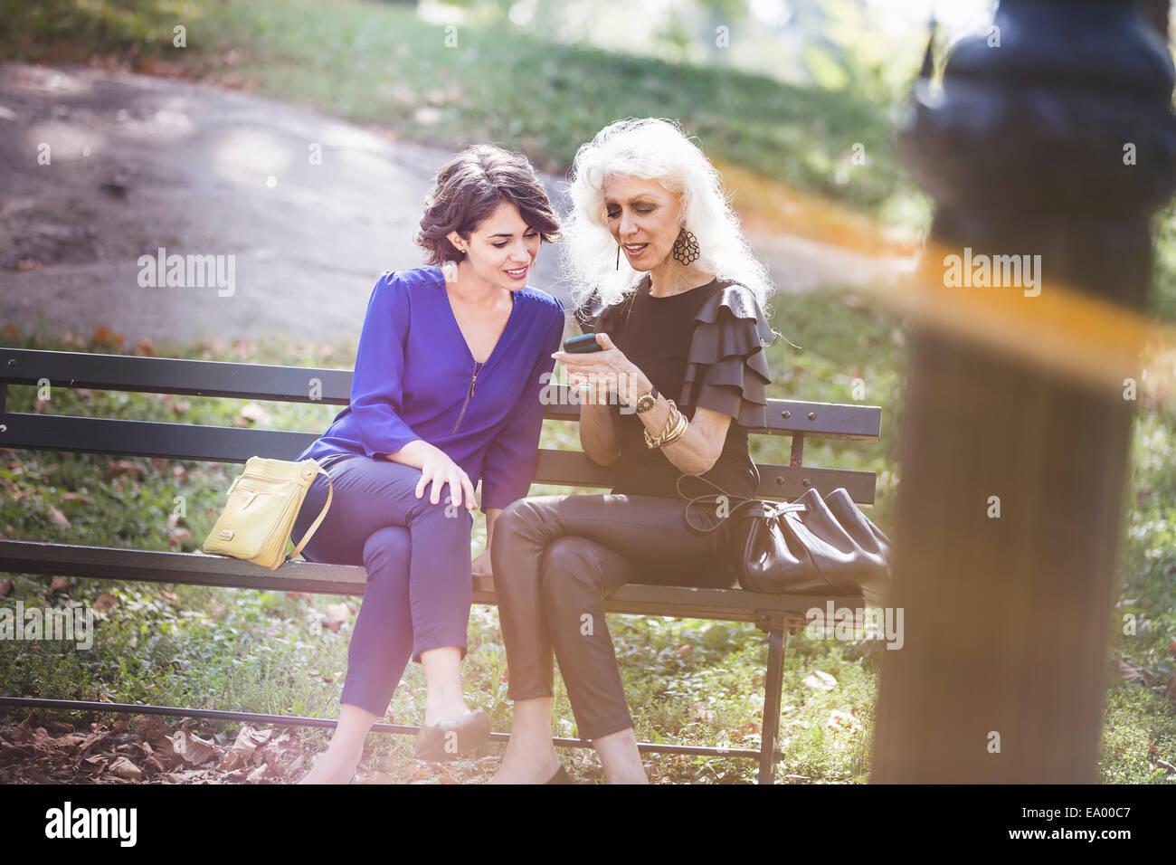 Mujer joven en el parque de la ciudad con el mentor mirando fotos en el smartphone Imagen De Stock