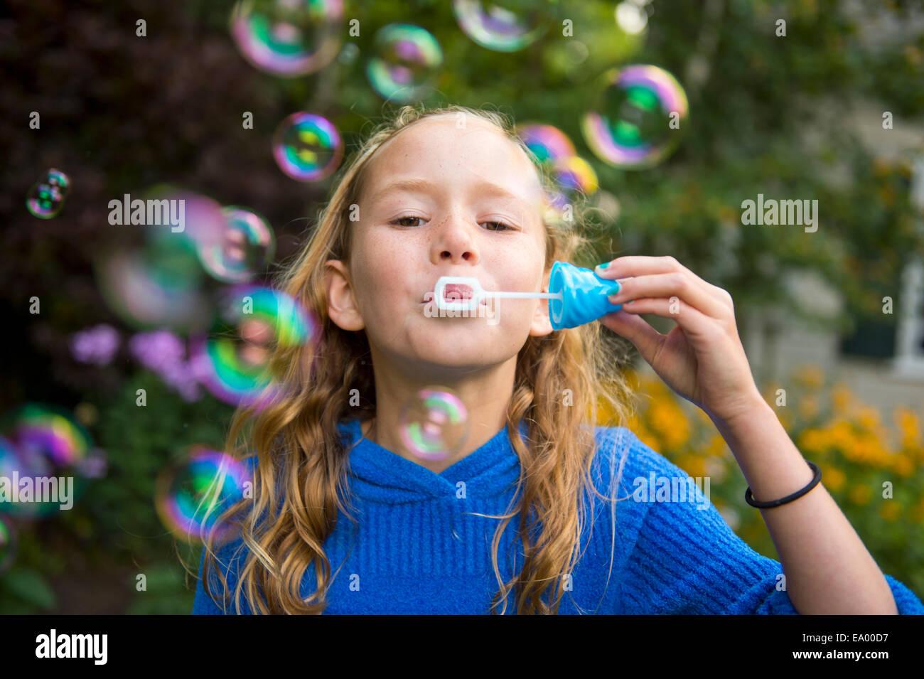 Niña soplando burbujas en el jardín Imagen De Stock