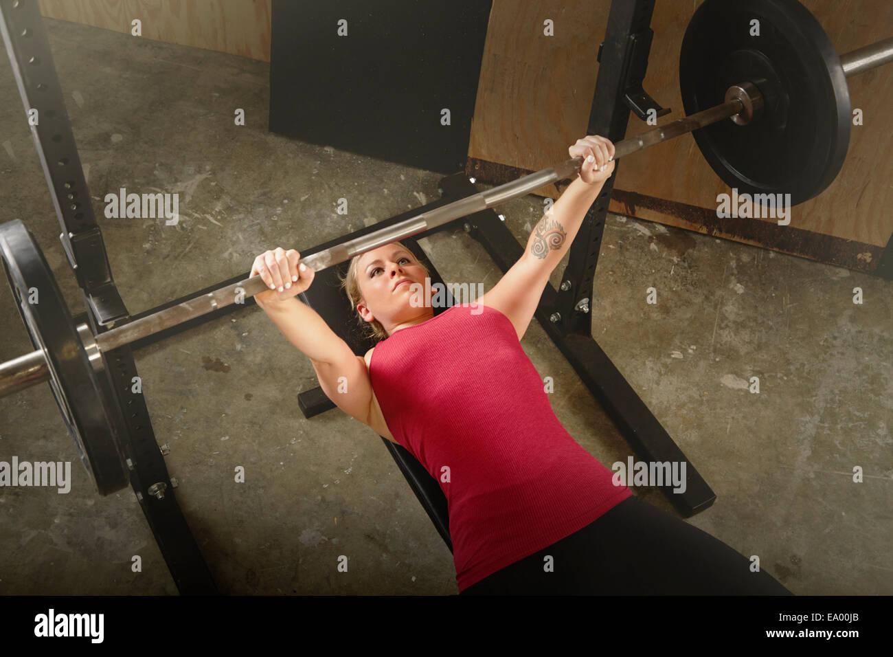 Mitad hembra adulto levantador de pesas levantamiento barbell en gimnasio Imagen De Stock