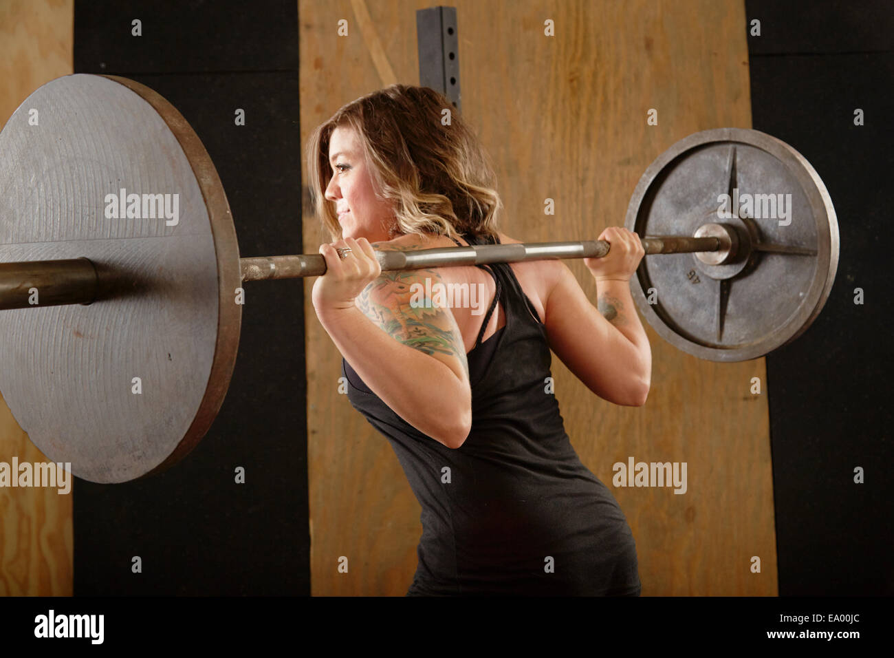Mujer joven levantando barbell en gimnasio Imagen De Stock