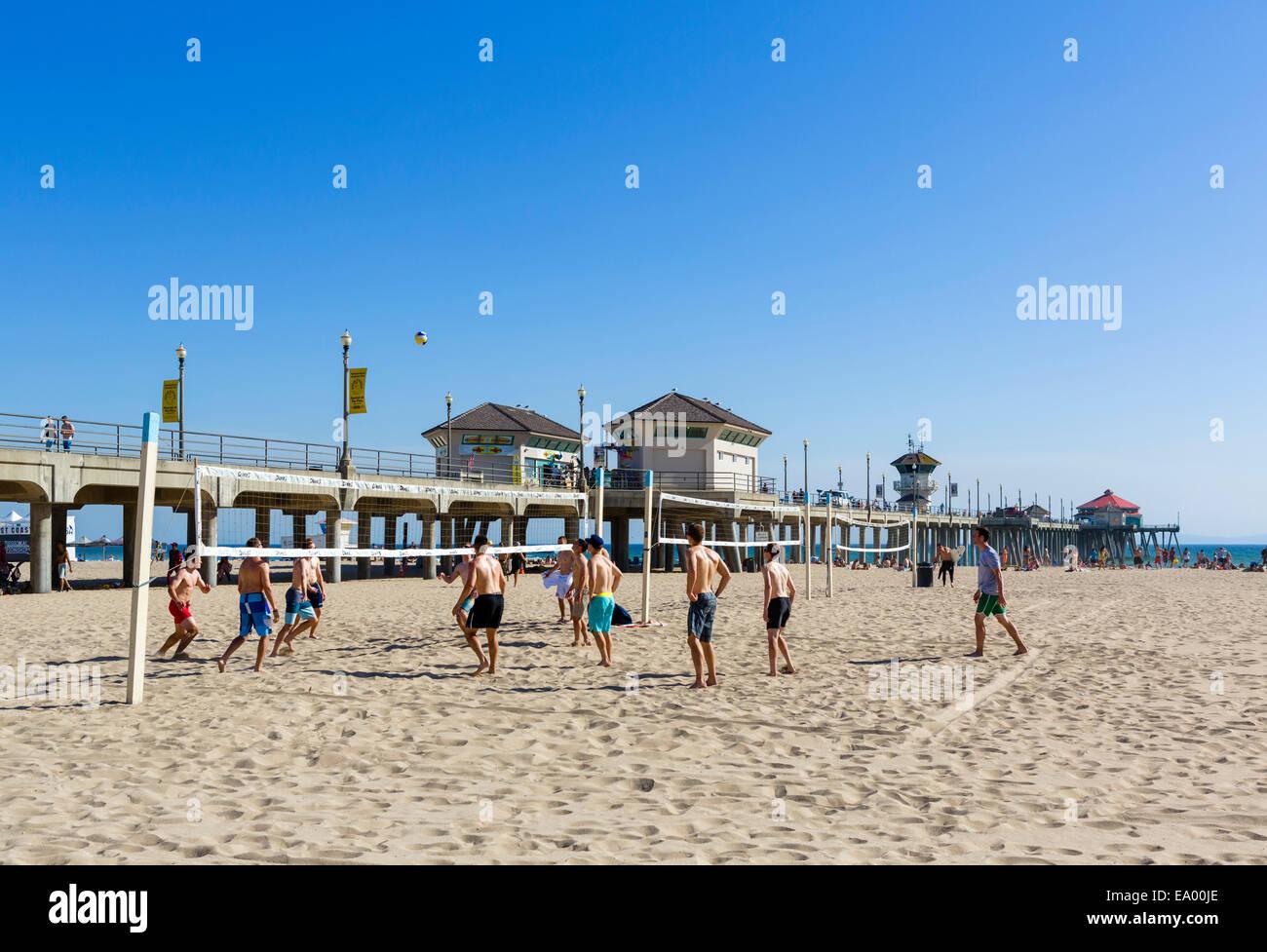 Los hombres jóvenes jugando voleibol en la playa en frente del muelle en el centro de la ciudad de Huntington Imagen De Stock