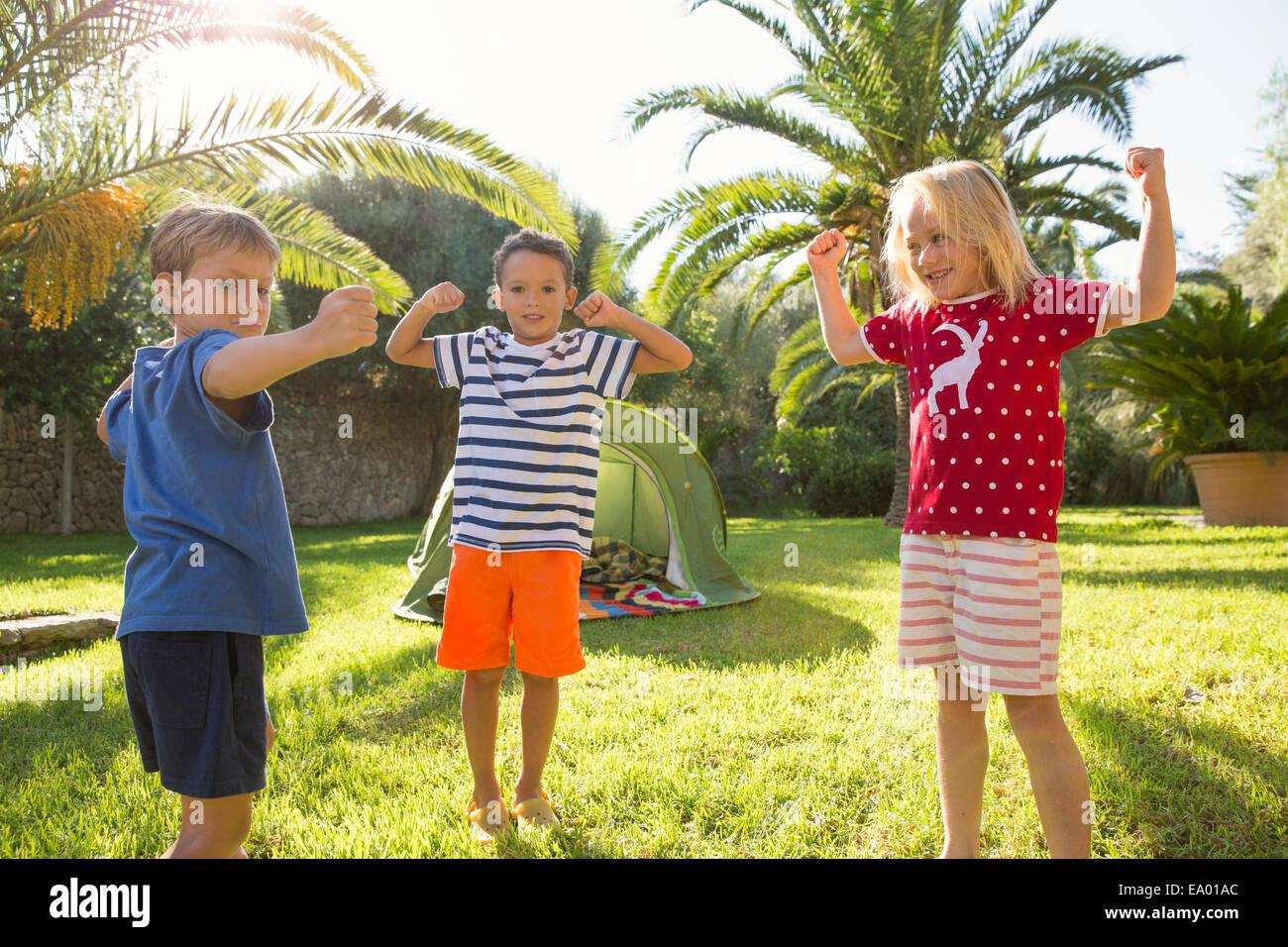 Tres niños en el jardín flexionando los músculos Foto de stock