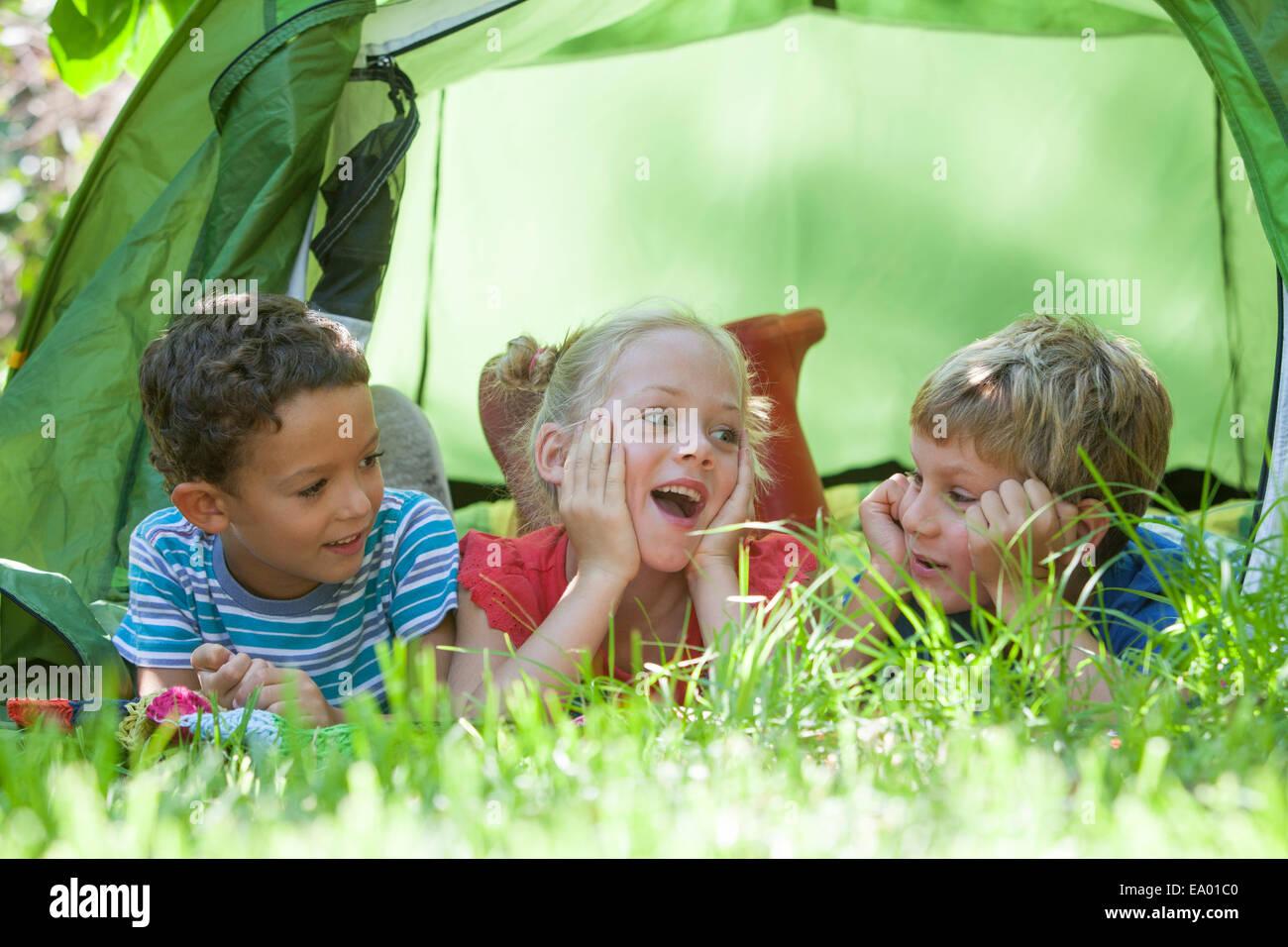 Tres niños acostado charlando en el jardín de su tienda Imagen De Stock