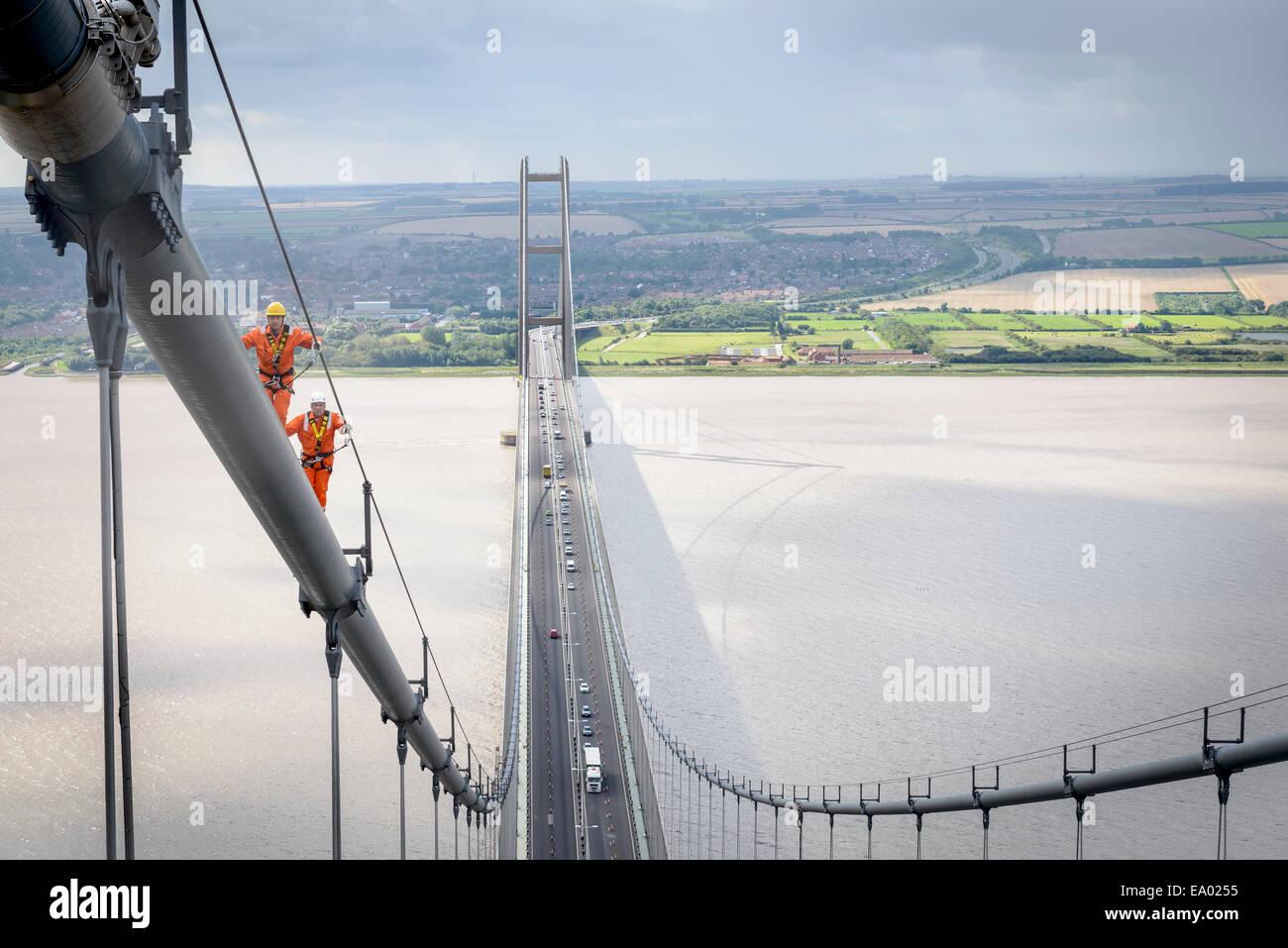 Los trabajadores de puente caminando sobre un cable de puente colgante Puente Humber fue construida en 1981 en el Imagen De Stock