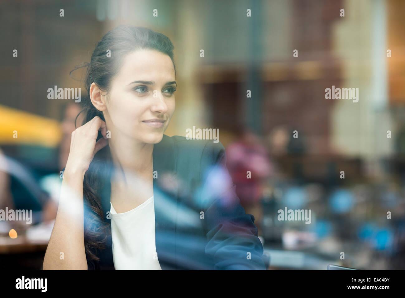 La empresaria mirando por la ventana café, Londres, Reino Unido. Imagen De Stock