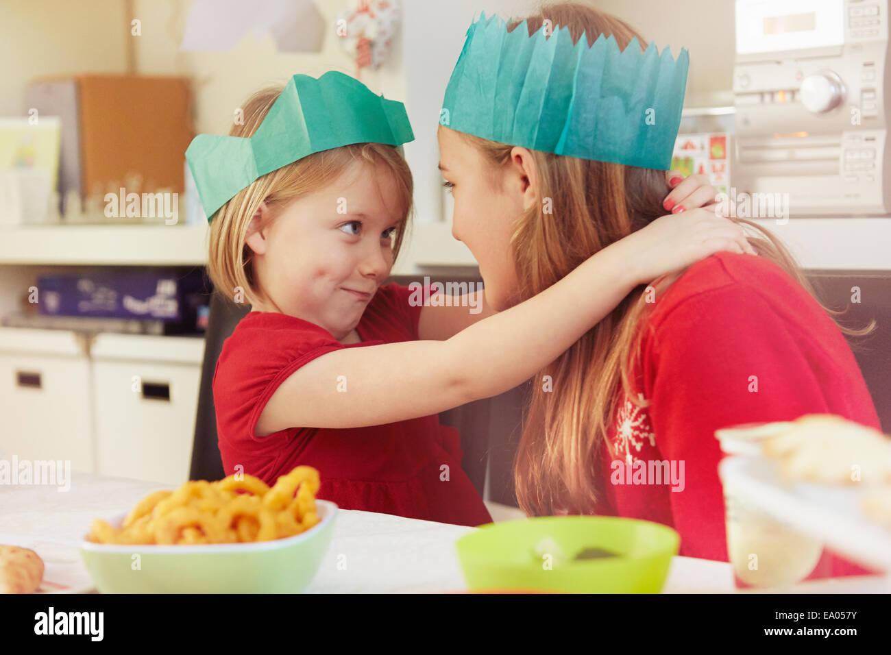 Hermanas en coronas de papel, un abrazo Imagen De Stock