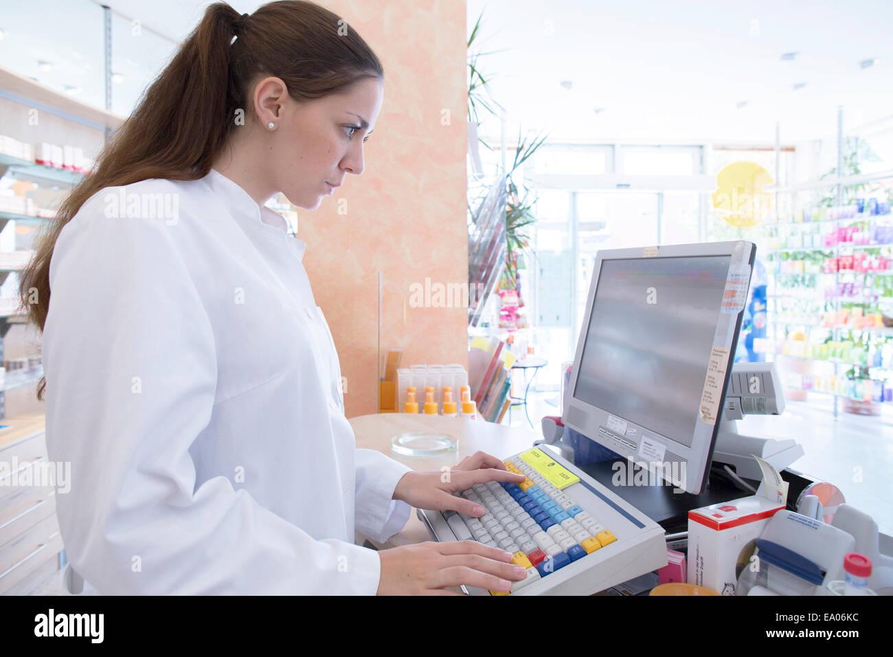 Farmacéutico en la farmacia a través de equipo Imagen De Stock