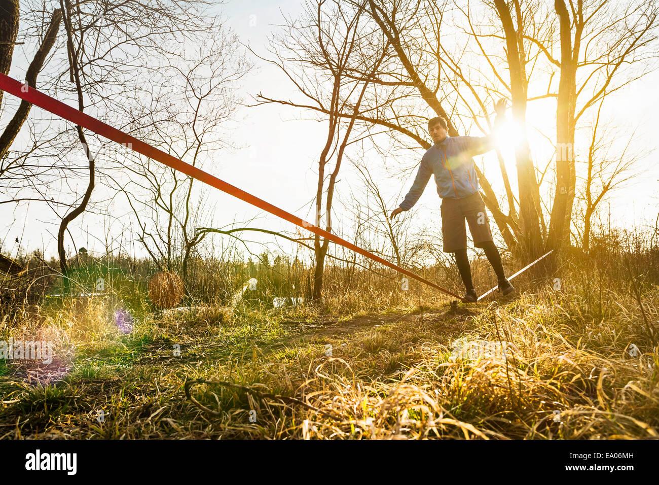 Joven el equilibrio sobre una pierna en slackline en paisaje de campo Imagen De Stock