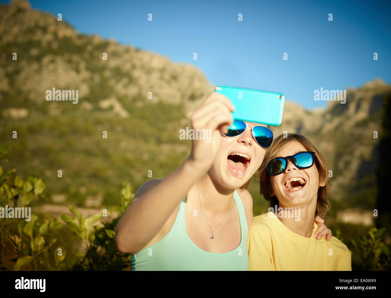 El hermano y la hermana haciendo caras selfie en smartphone, Mallorca, España Foto de stock