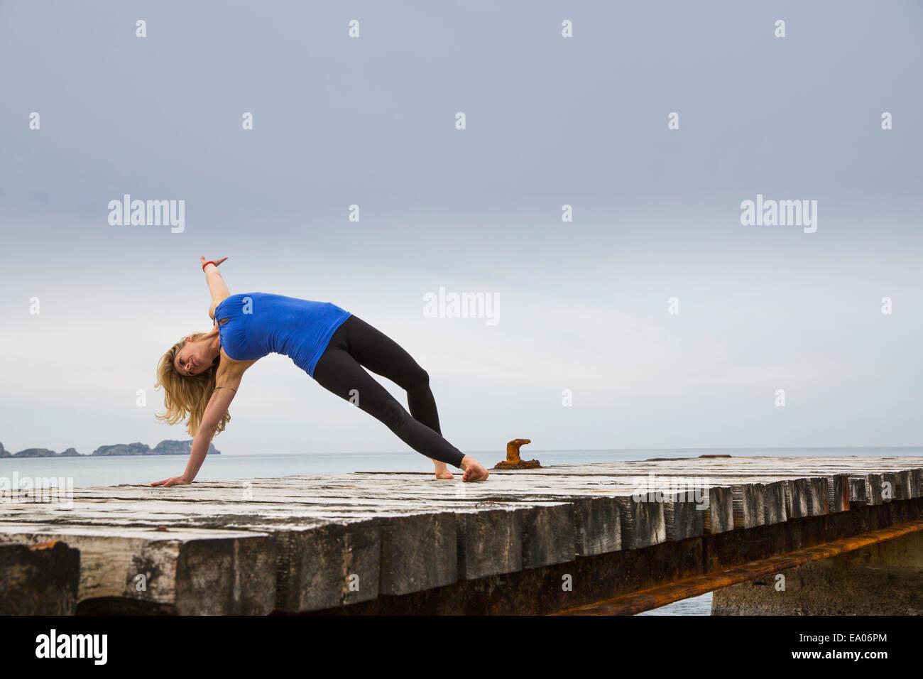 Mitad mujer adulta practicando yoga se mueven en Mar del muelle de madera Imagen De Stock