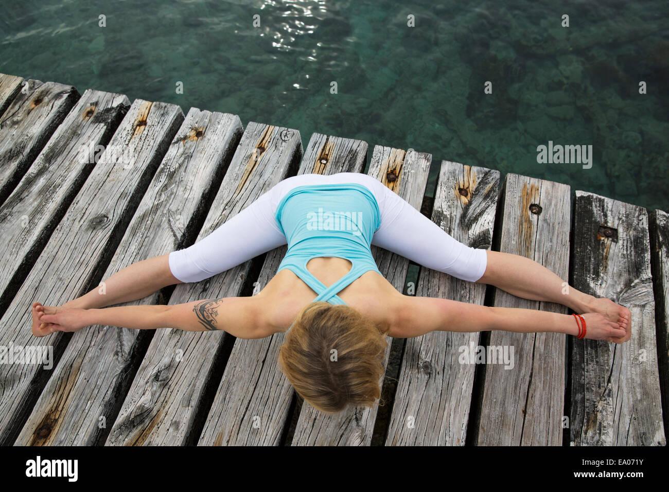Vista aérea de mediados de mujer adulta con brazos y piernas extendidas practicando yoga en Mar del muelle Imagen De Stock