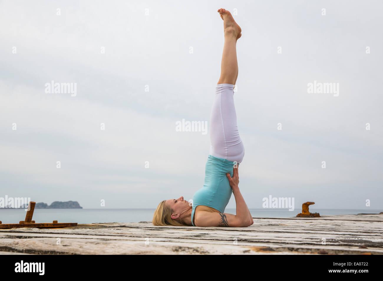 Mitad mujer adulta con piernas levantadas practicando yoga en Mar del muelle de madera Imagen De Stock