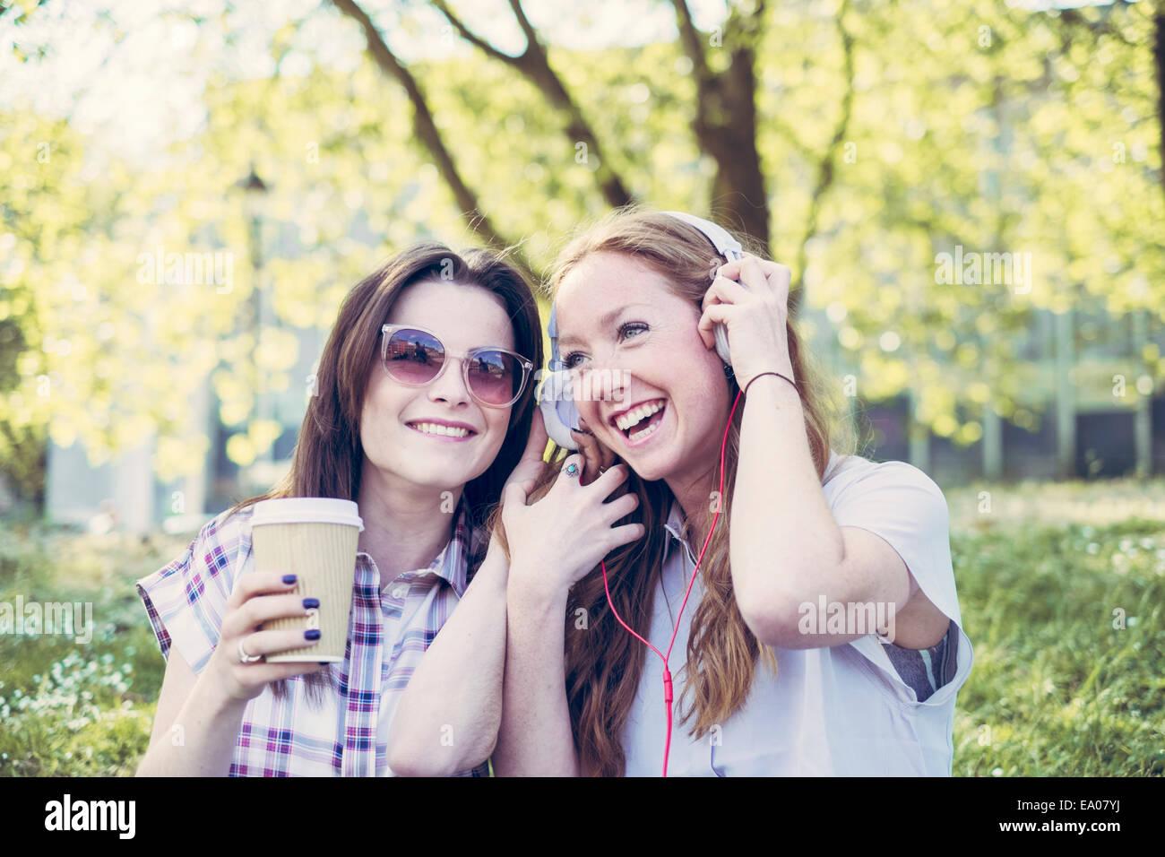 Dos amigas jóvenes bebiendo café y escucha música con los auriculares en el parque Imagen De Stock