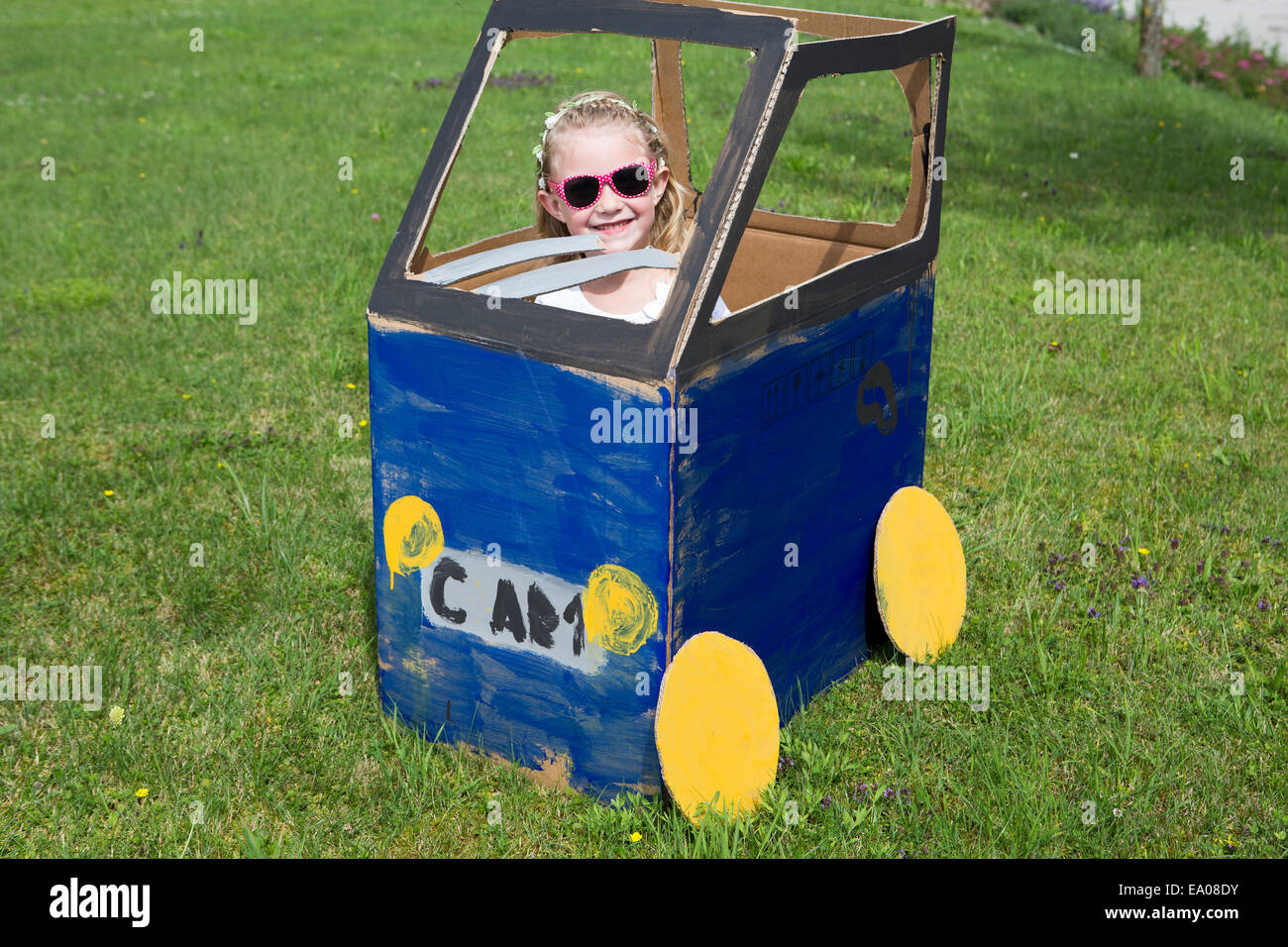Niña jugando en casero coche de juguete Foto de stock
