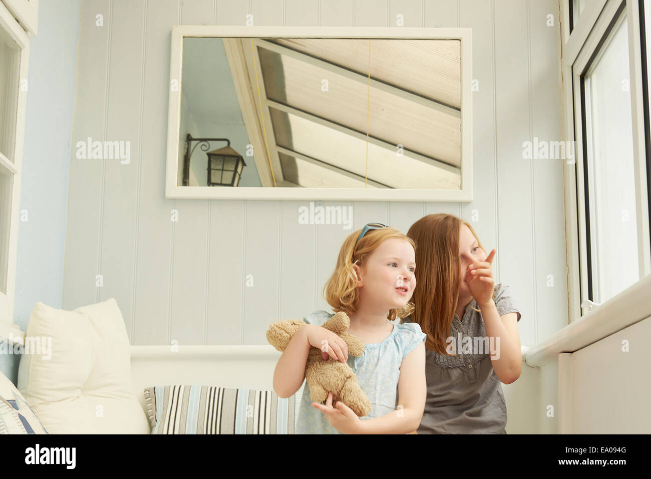 Dos hermanas apuntando y mirando por la ventana del apartamento de vacaciones Imagen De Stock