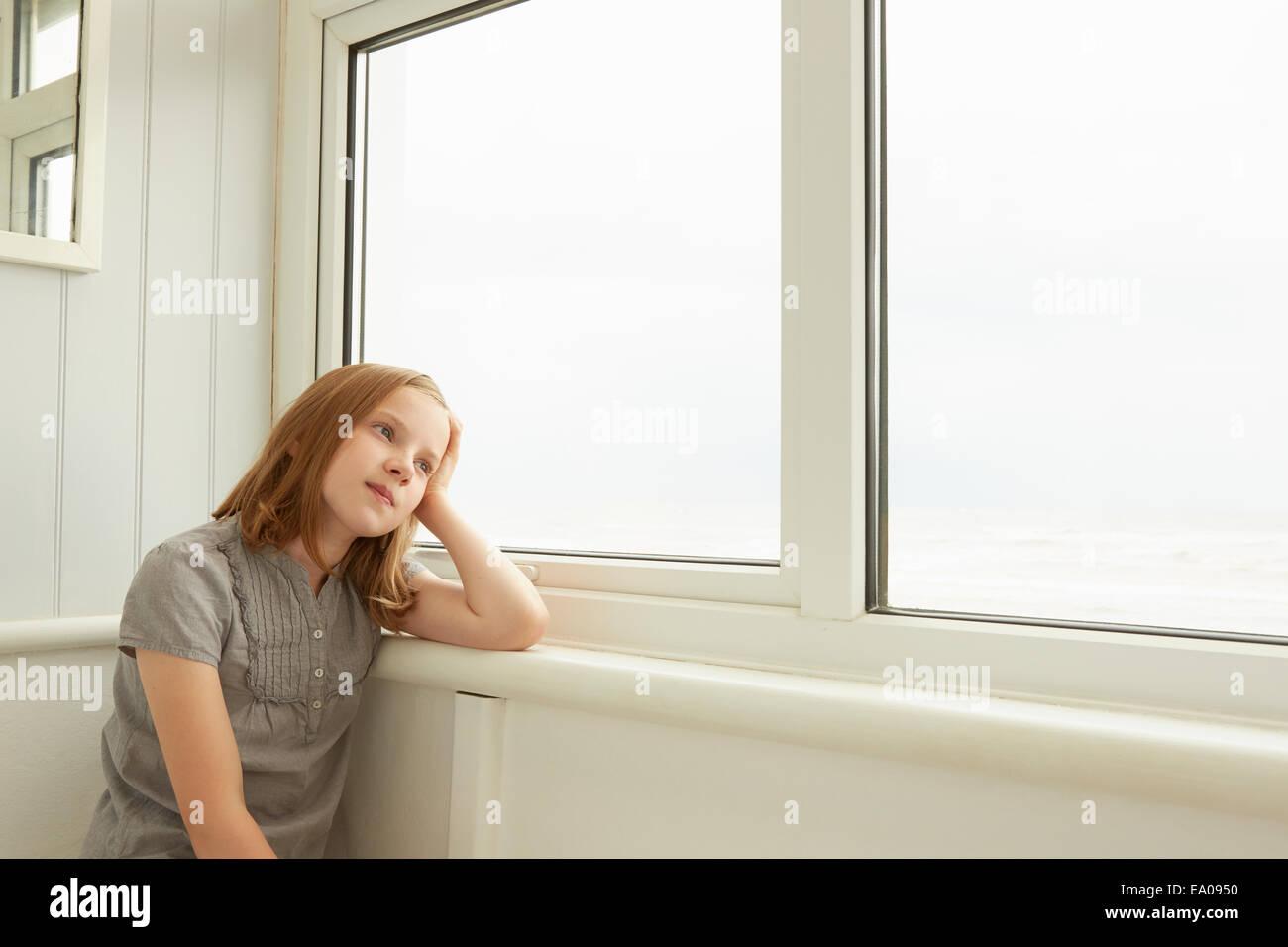 Retrato de niña mirando por la ventana apartamento Imagen De Stock
