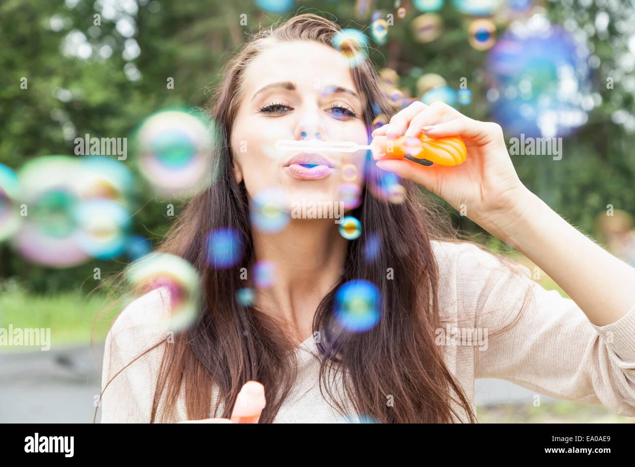 Mujer joven soplando burbujas Imagen De Stock