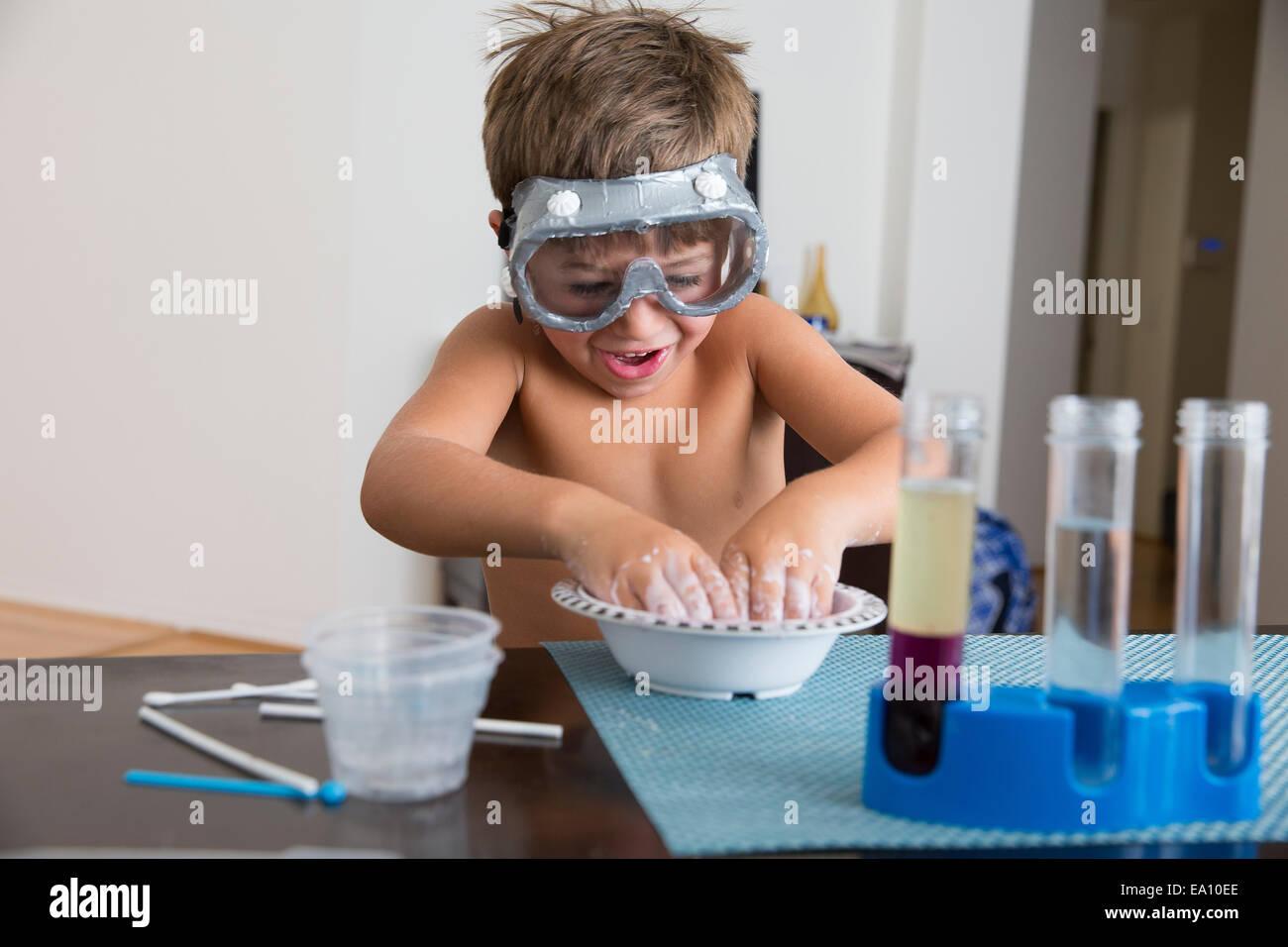 Chico en gafas jugando con la mezcla en un tazón Imagen De Stock