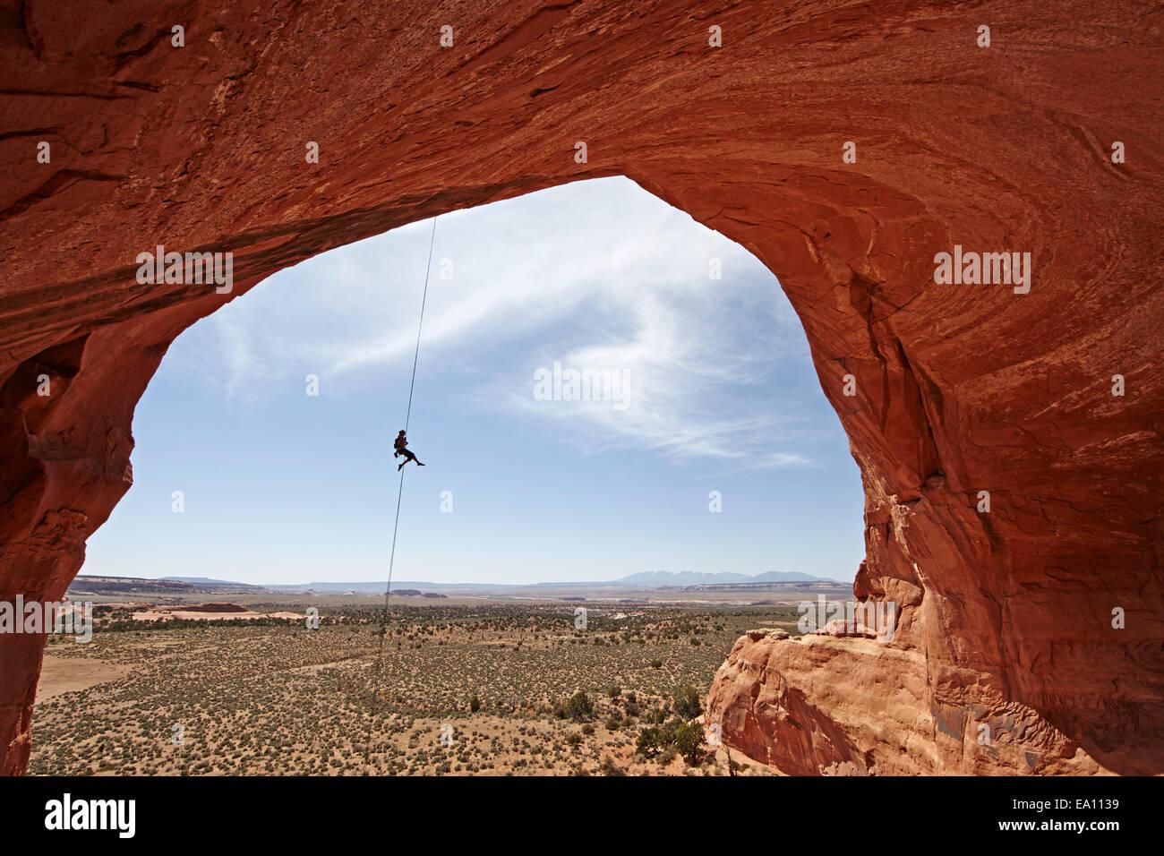 Mujer rappel desde arch, Moab, Utah, EE.UU. Imagen De Stock