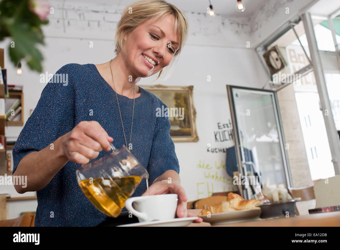 Mujer adulta media vertiendo té en el cafe Imagen De Stock