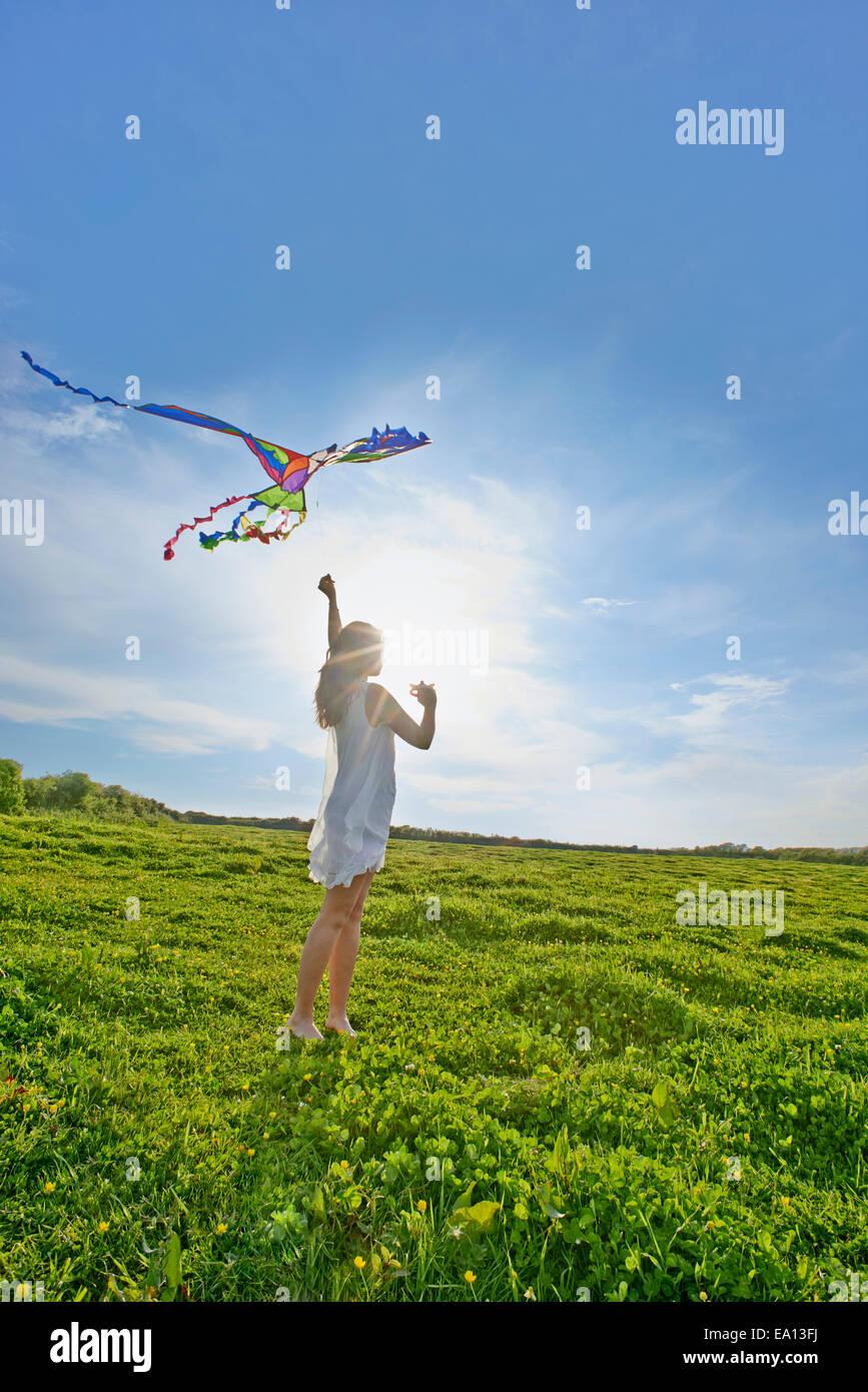 Mujer joven volar una cometa en el campo Imagen De Stock
