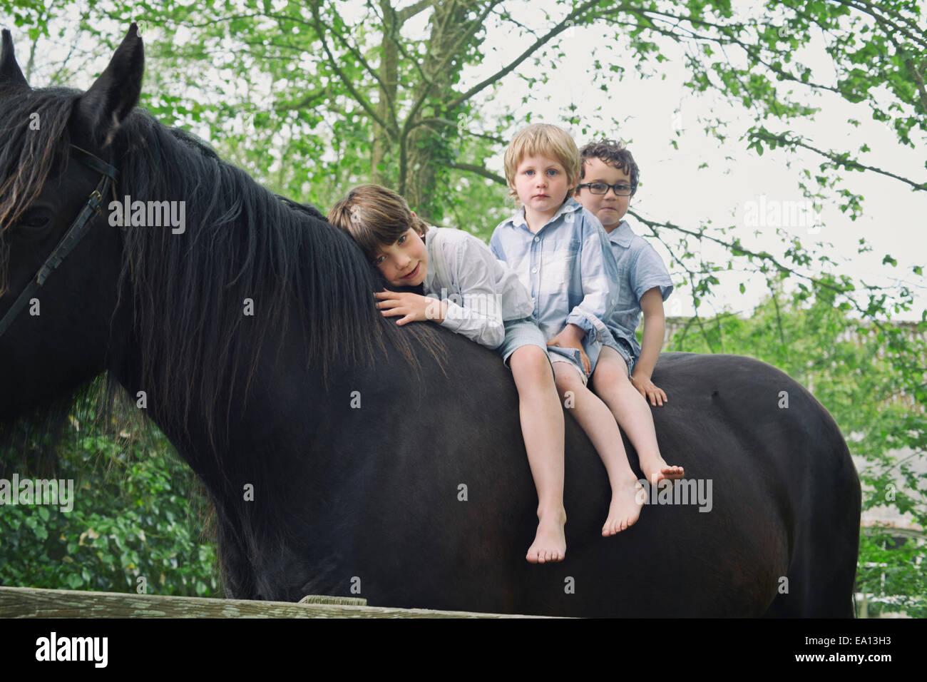 Tres muchachos en una fila de rutas a caballo en los bosques Imagen De Stock