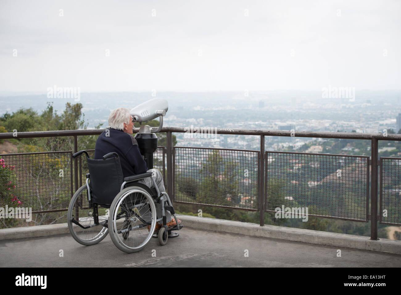 Hombre senior en silla de ruedas mirando a través de la ciudad con monedas binoculares desde un mirador Observatorio Imagen De Stock