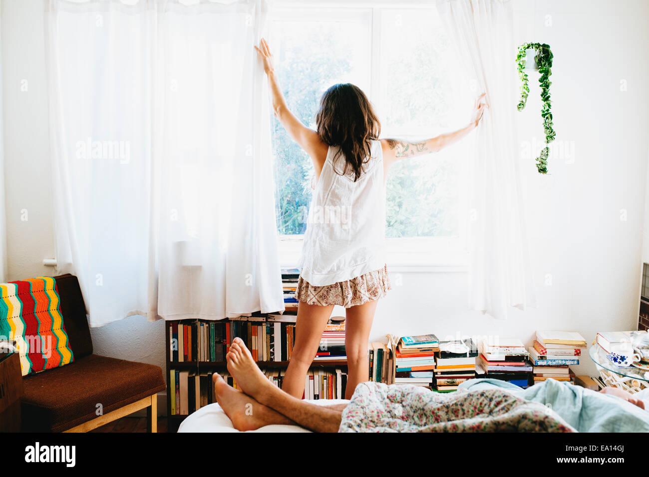 Mujer sacando cortinas abiertas Imagen De Stock