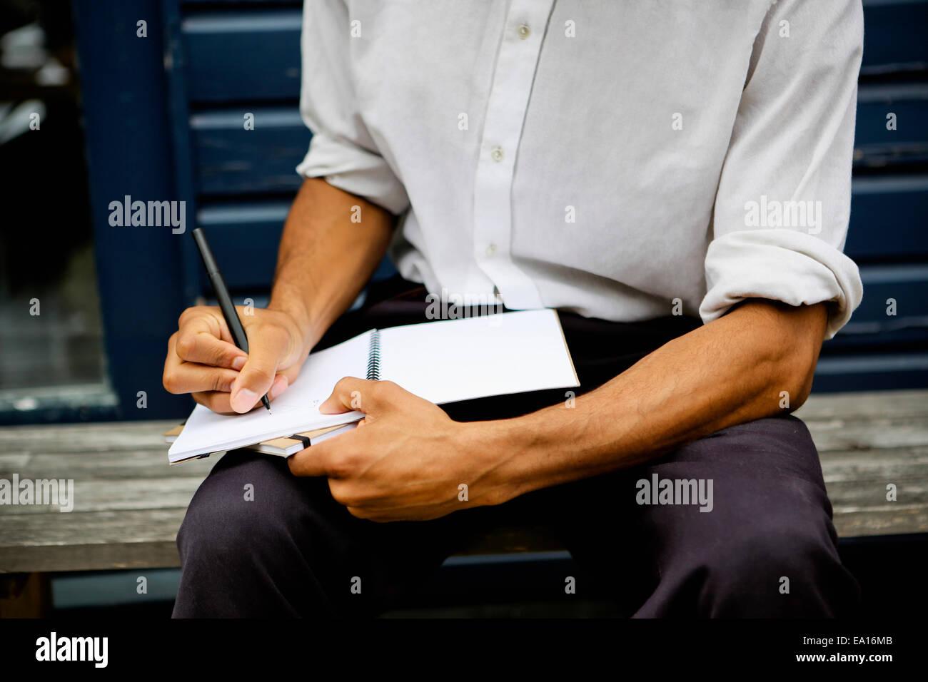 Hombre escrito en el bloc de notas Imagen De Stock
