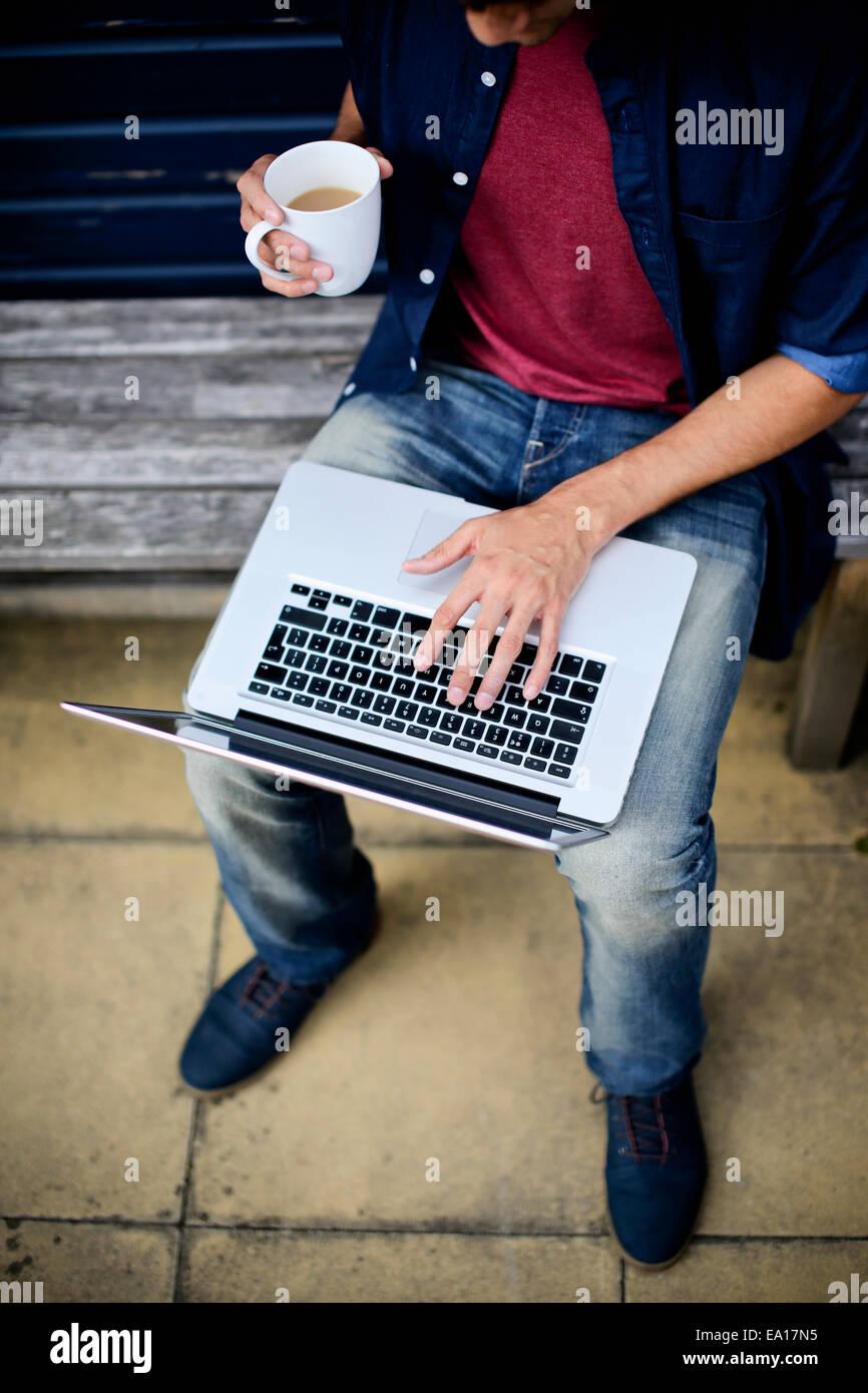 Hombre utilizando el portátil en un banco Foto de stock