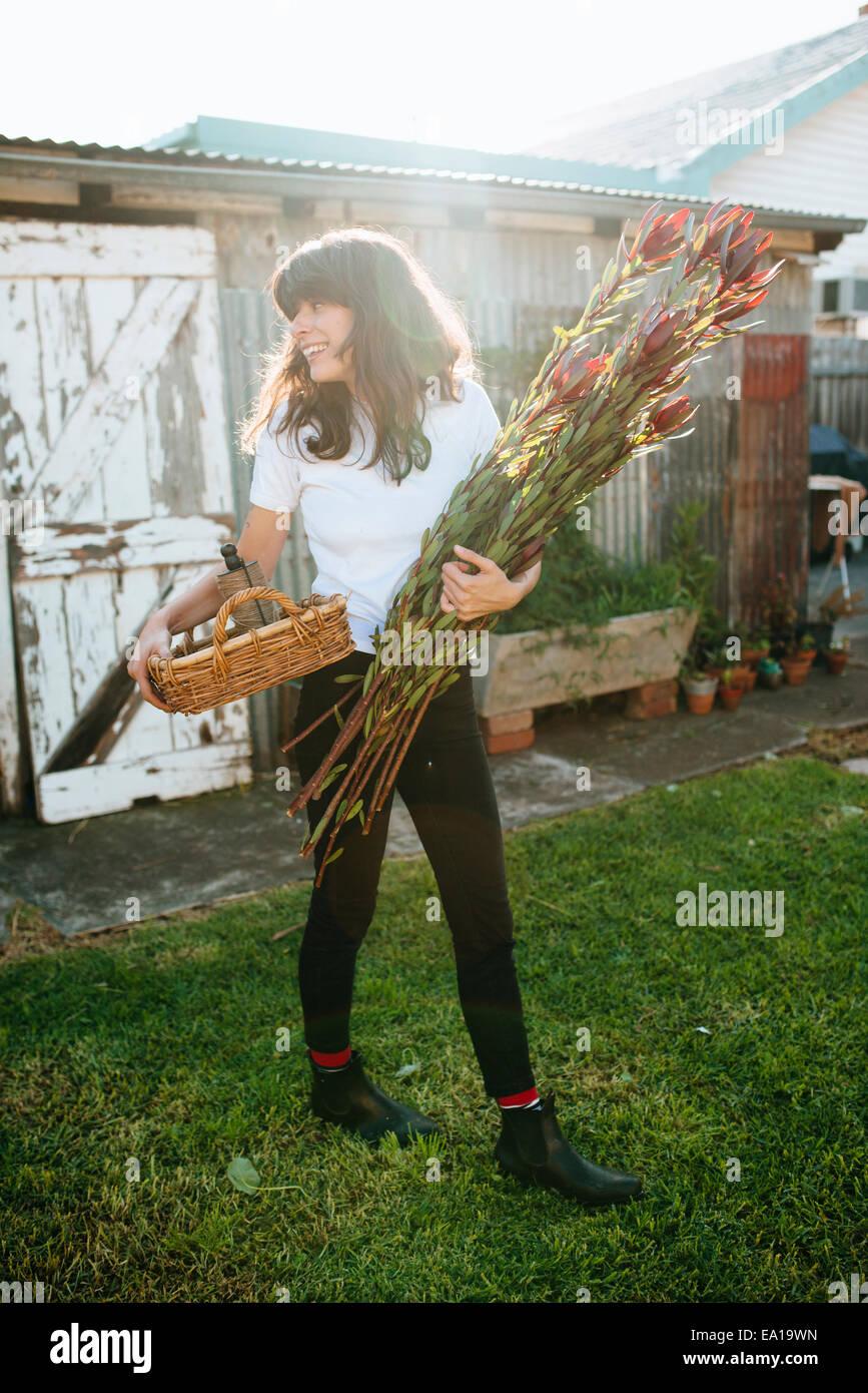 Mujer recogiendo flores en el jardín autóctono Imagen De Stock