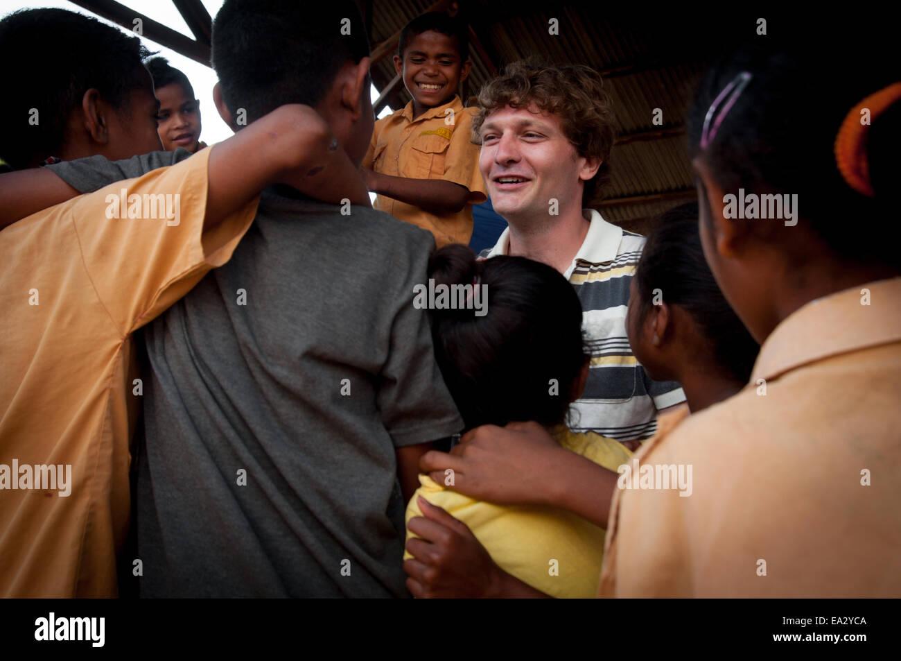 Un hombre occidental hablando a los niños locales en Labalimut village, Lembata Isla, Indonesia. Imagen De Stock
