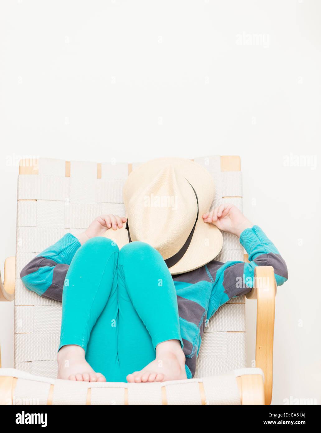 Chica 4-5 años sentados en una silla y ocultar rostro detrás de un sombrero. Imagen De Stock